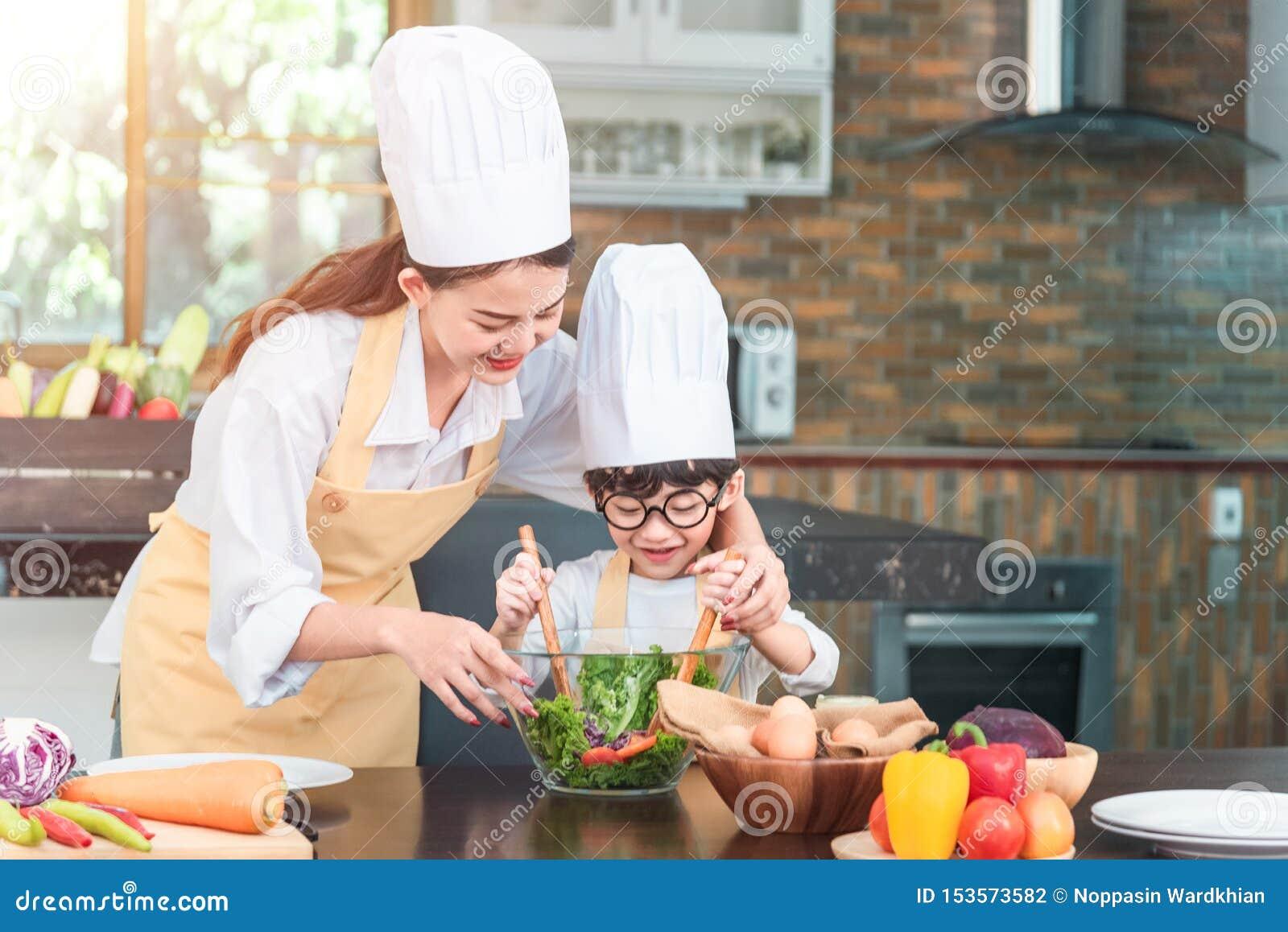 烹调沙拉的妈妈和他的小女儿博洛涅塞调味汁在厨房,那里是逃脱从在烹调的平底锅的蒸汽