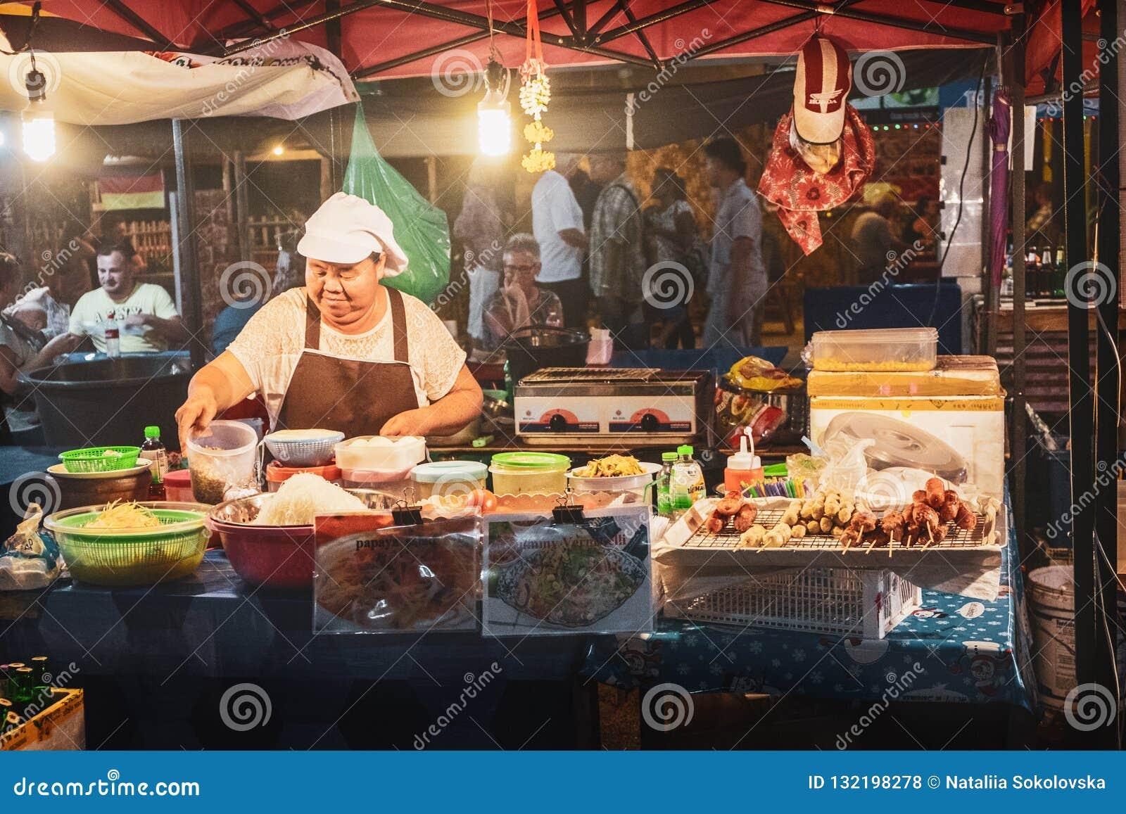 烹调番木瓜沙拉的泰国妇女在街市上