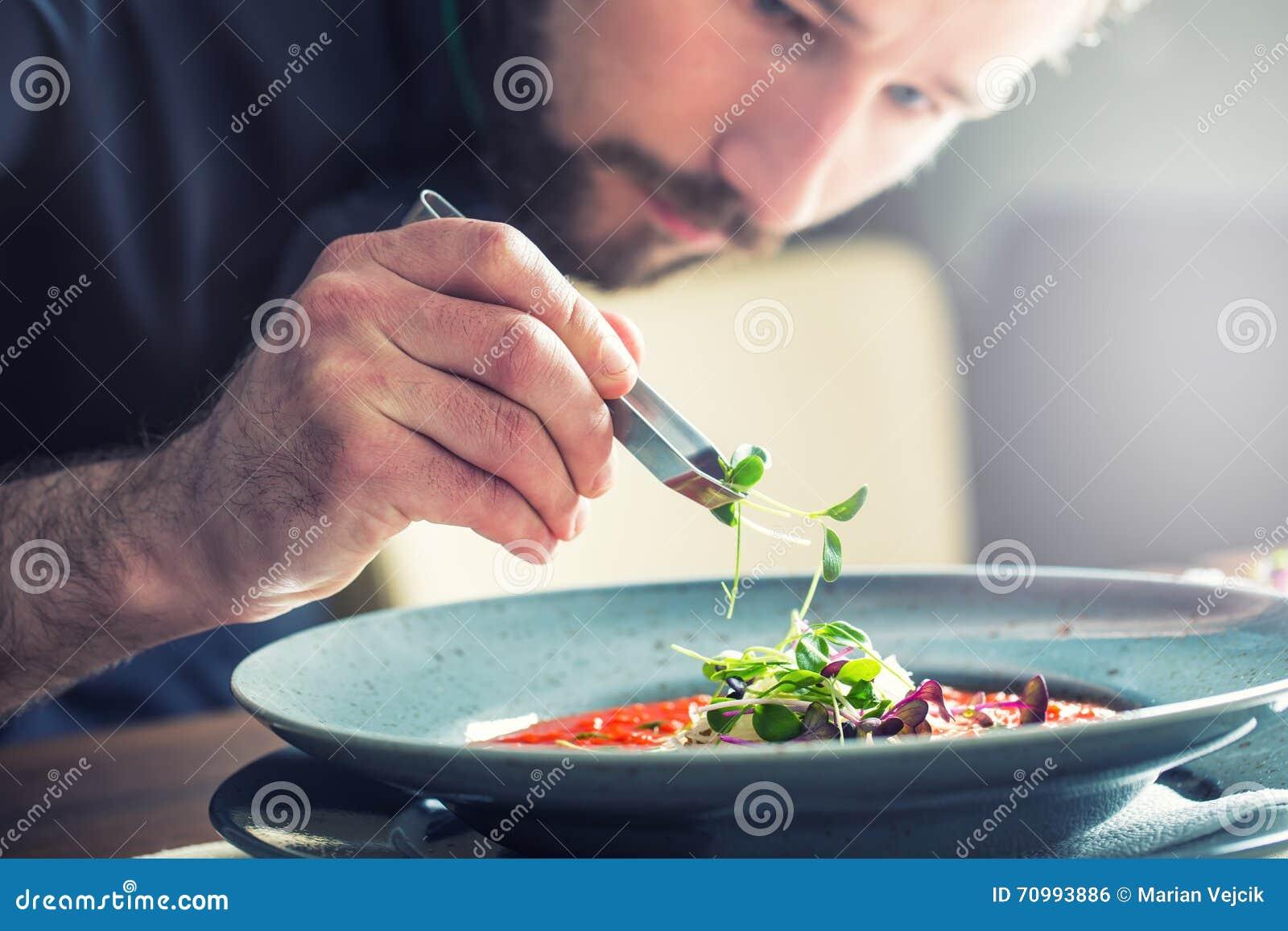 烹调的厨师在旅馆或餐馆厨房里,仅手 他在微草本装饰工作 准备蕃茄汤