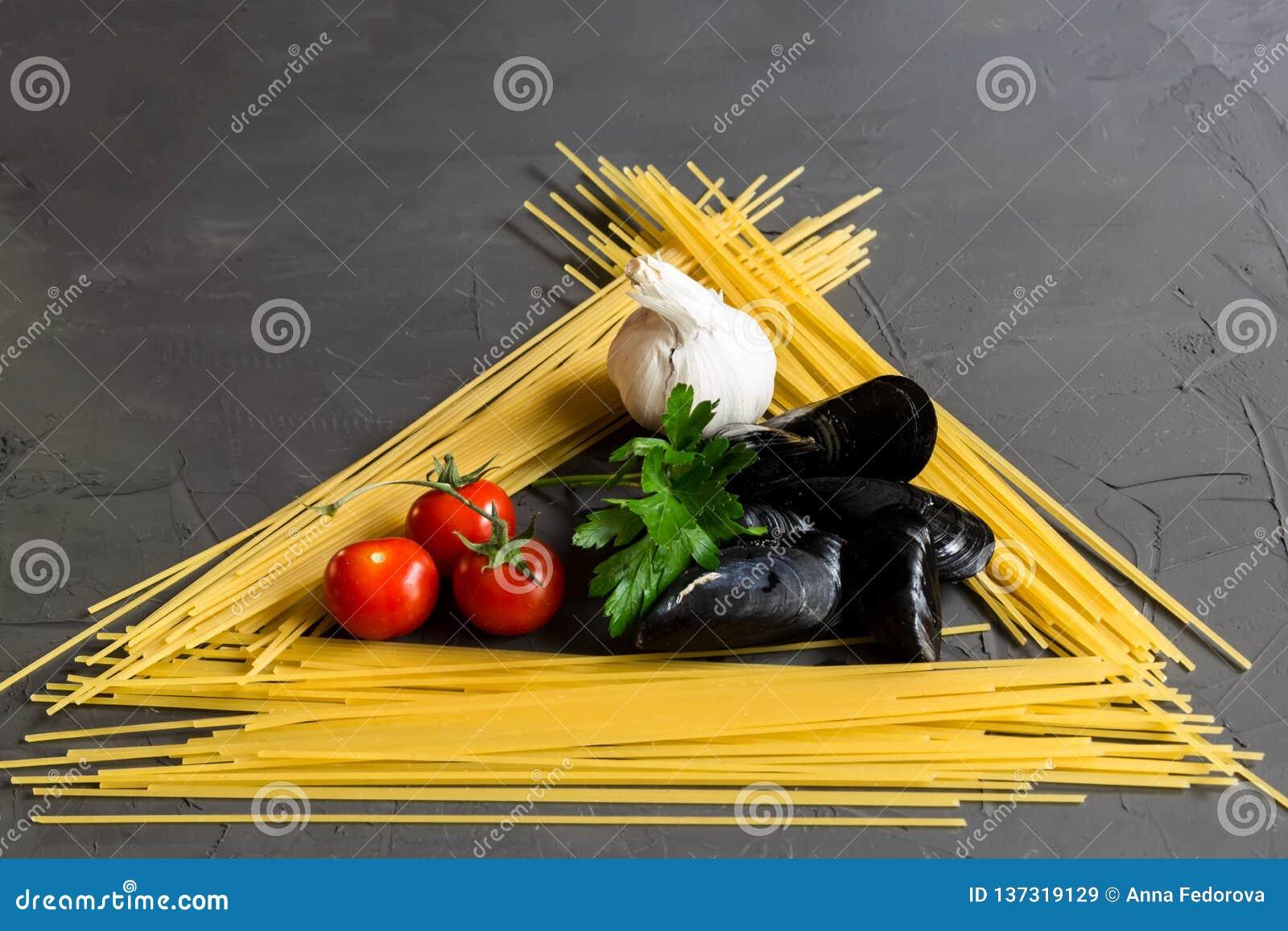 烹调的意粉和淡菜,蕃茄,大蒜,在灰色背景的荷兰芹,顶视图,平的位置新鲜的成份