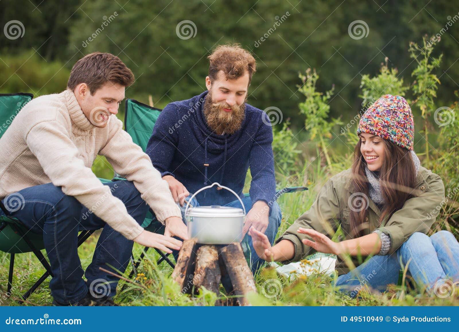 烹调食物的小组微笑的朋友户外