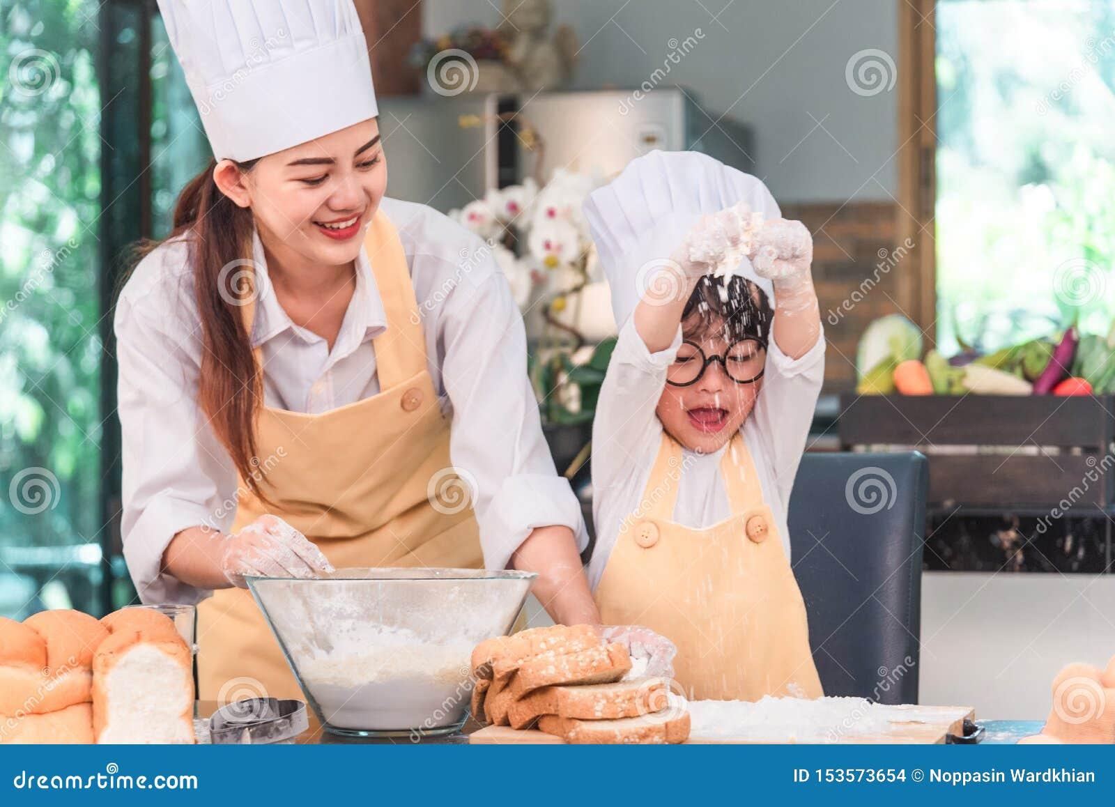 烹调食物的年轻家庭在厨房里 有她的母亲混合的面团的愉快的少女在碗