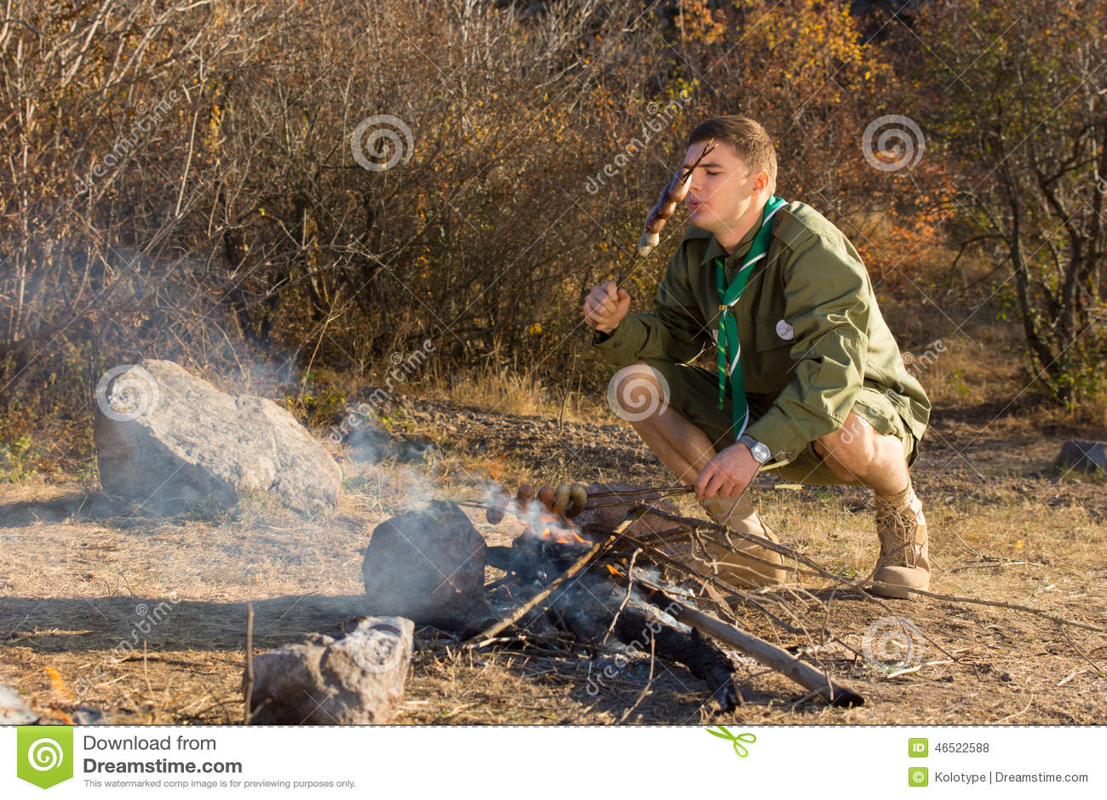 烹调香肠的饥饿的年轻人侦察员