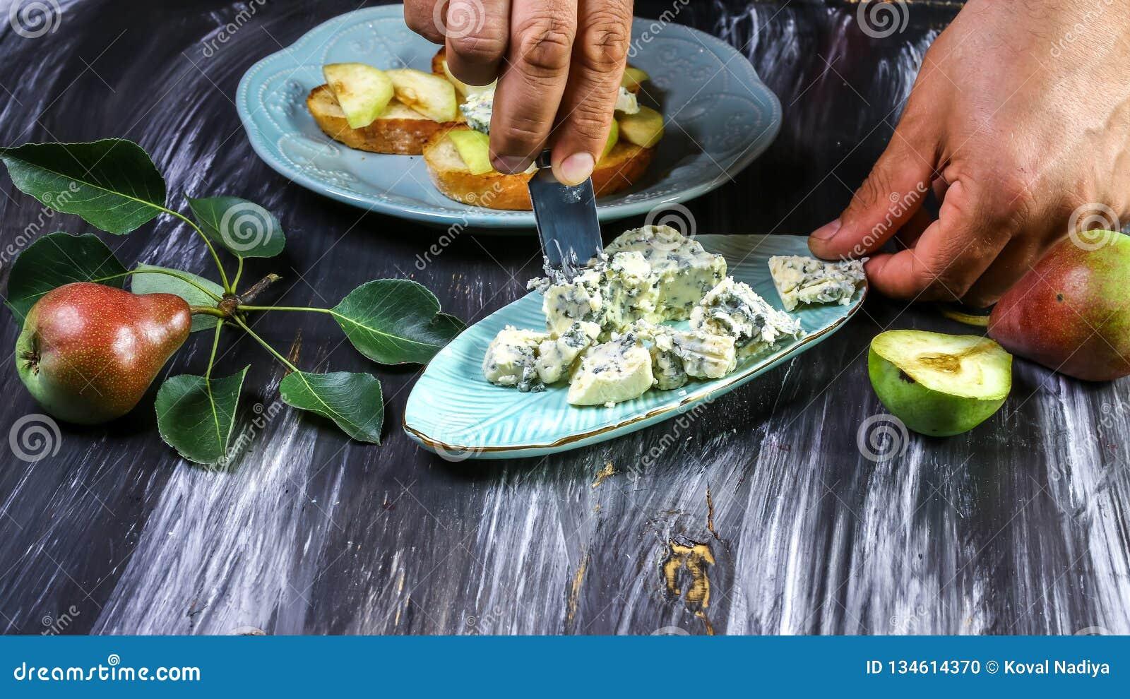 烹调bruschetta用梨,乳酪和蜂蜜五谷总体上烤了面包-在深黑色背景 在倾吐的餐馆沙拉的主厨概念食物新鲜的厨房油橄榄