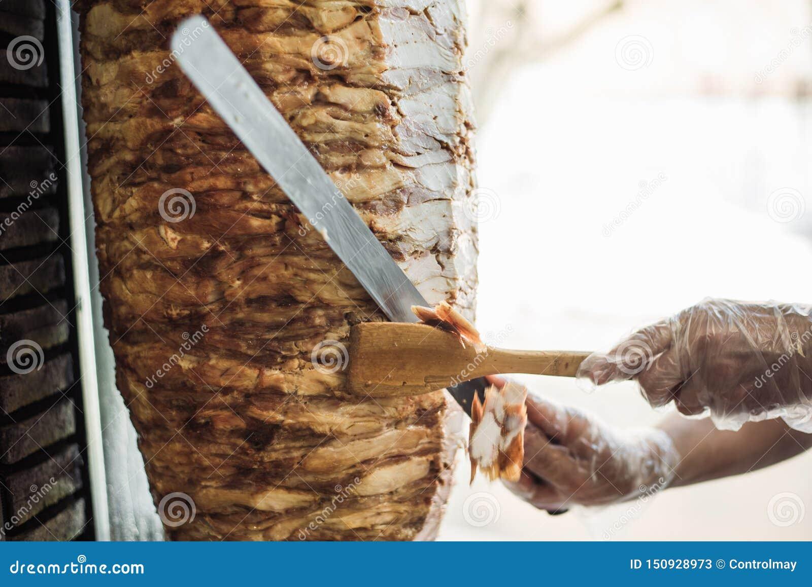 烹调shawarma和ciabatta在咖啡馆 一次性手套裁减肉的一个人在串