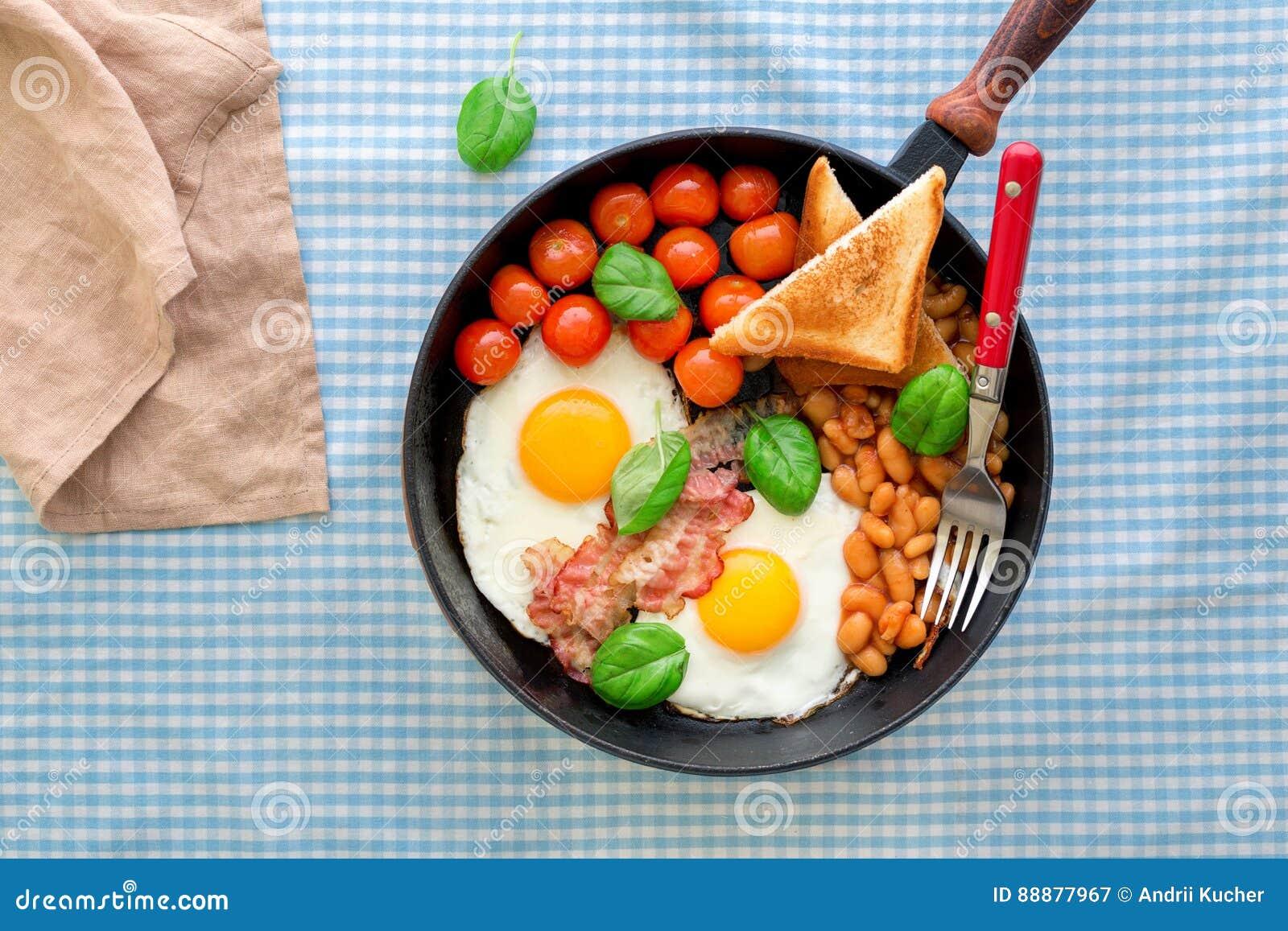 煎蛋、豆、蕃茄、烟肉和多士在平底锅