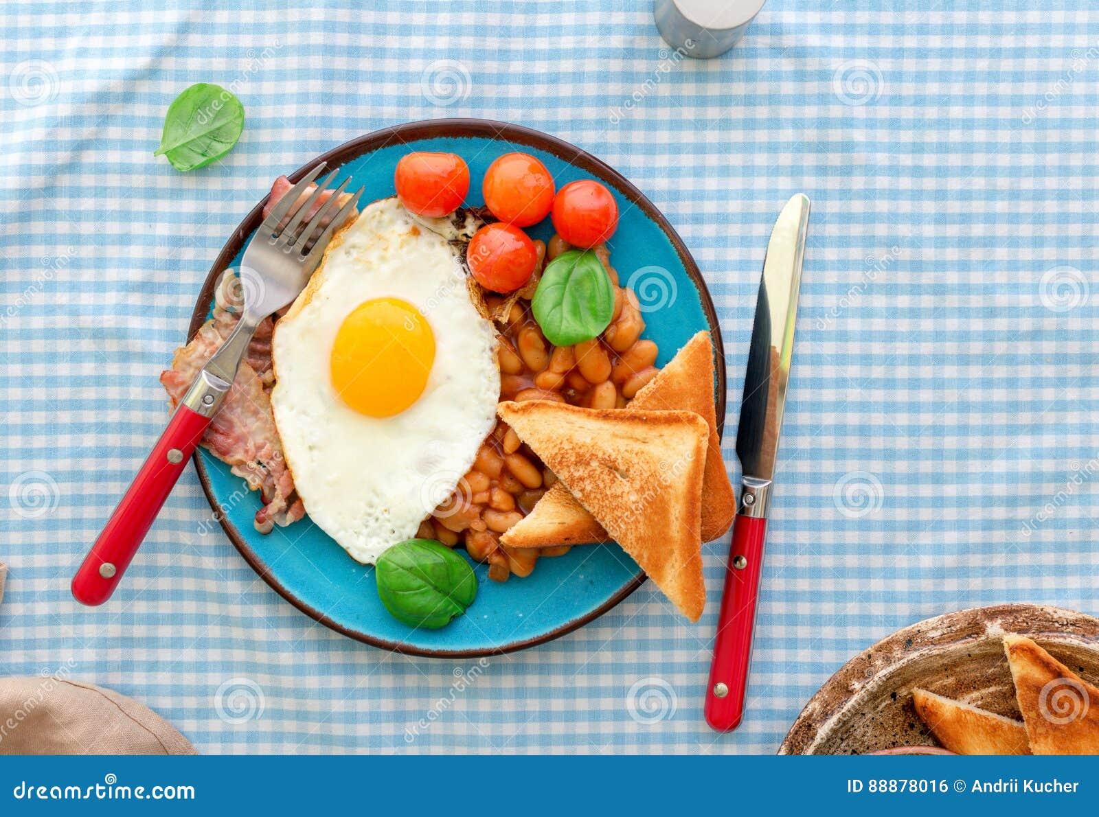 煎蛋、豆、蕃茄、烟肉和多士在板材