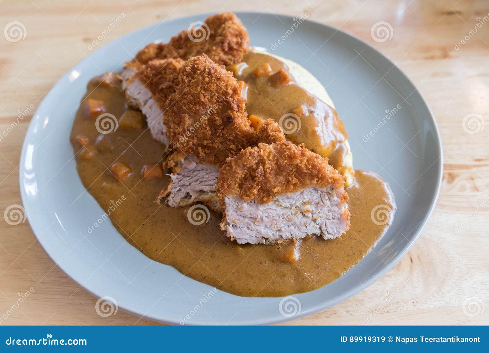 煎蛋卷米用日本咖喱和面包被油炸的猪肉炸肉排在现代木表上