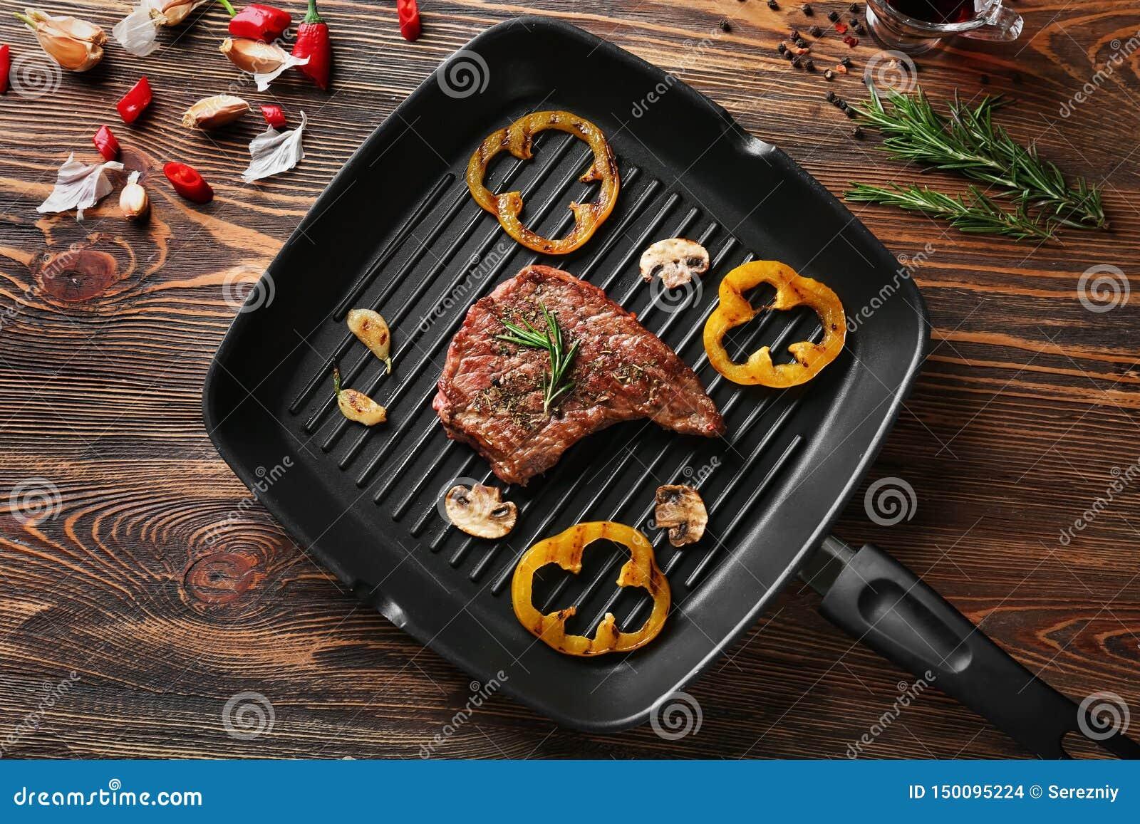 煎锅用可口烤牛排和菜在木桌上