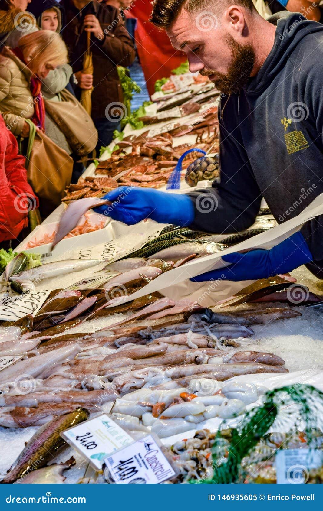 照应顾客的年轻白种人男性鱼市工作者在威尼斯大石桥市场,威尼斯,意大利上