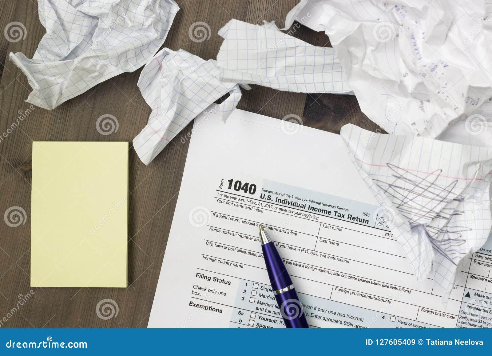 照片从上面美国联邦税务局报税表1040,黄色笔记、被弄皱的纸板料和一支笔在木桌上 顶面veiw, selectiv