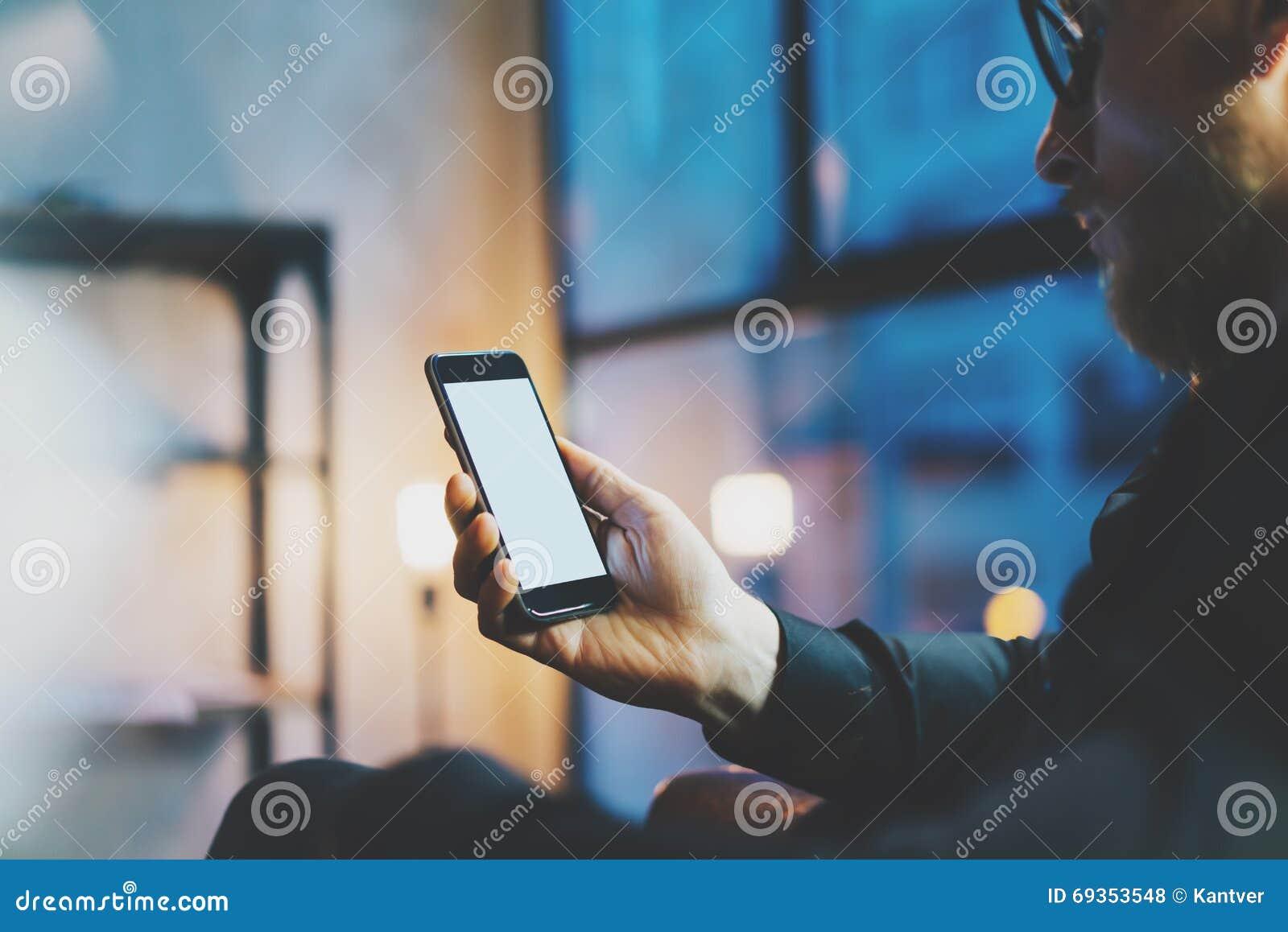 照片商人松弛现代顶楼办公室 人坐的椅子夜 使用当代智能手机,被弄脏的背景