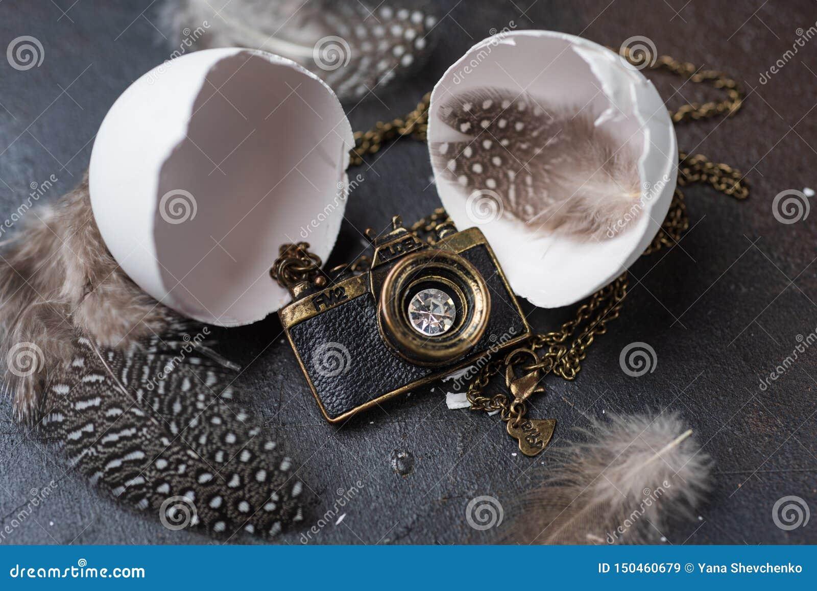 照片照相机塑造了从白色蛋壳孵化的垂饰