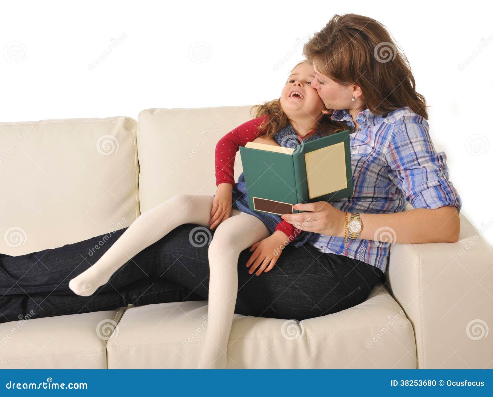 照顾亲吻和讲童话给逗人喜爱的矮小的女儿