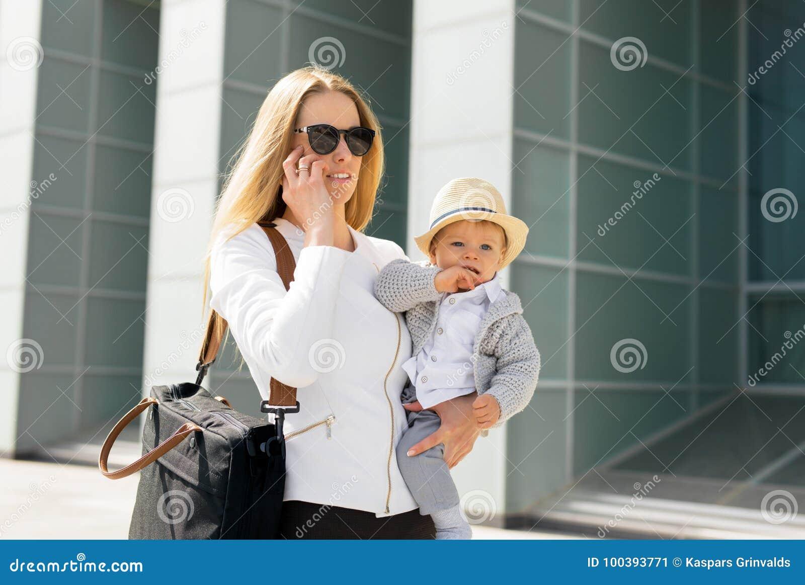 照顾去工作和谈话在有婴孩的电话在她的手上