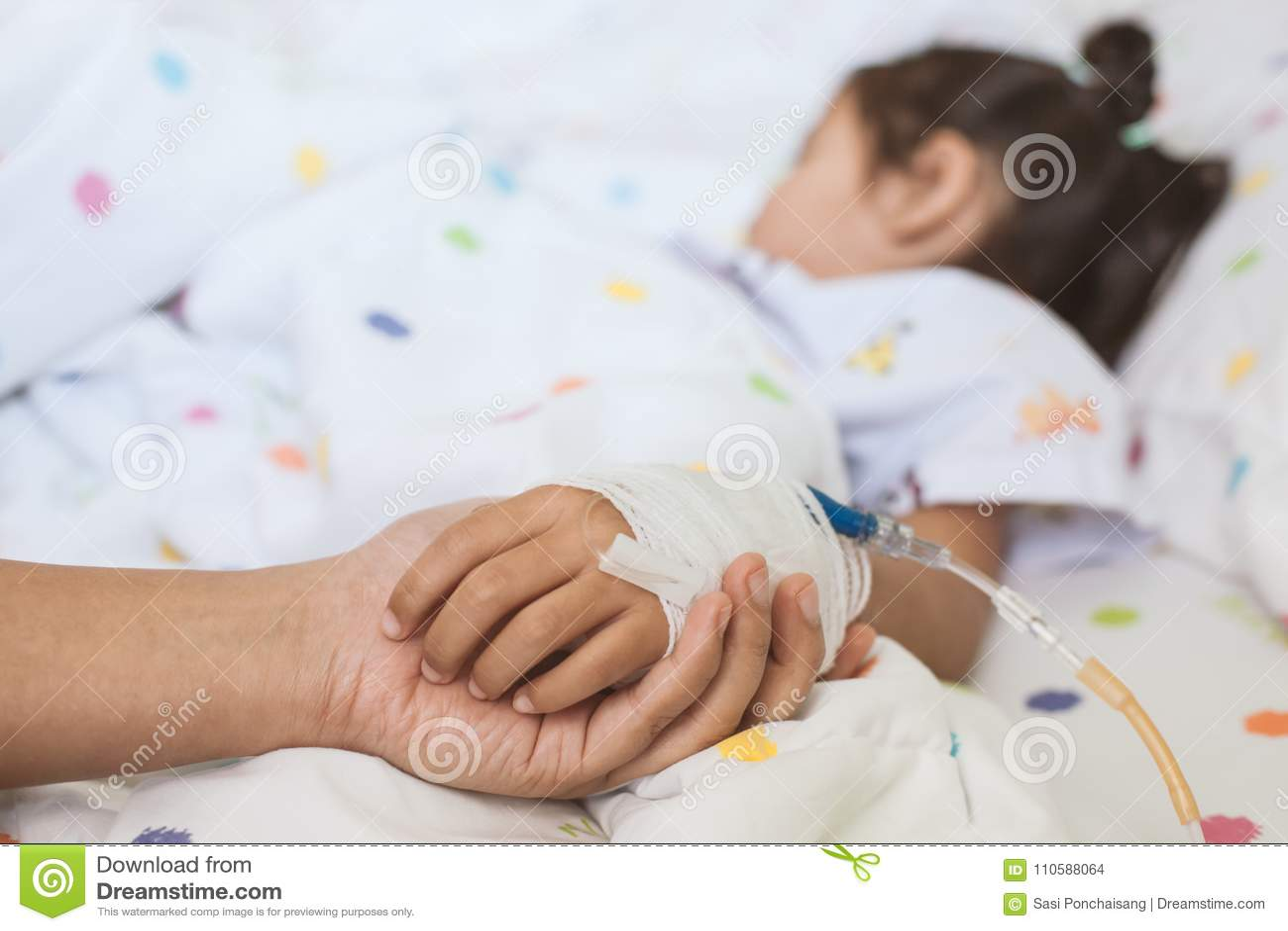 照顾握有IV解答的病态的女儿手的手
