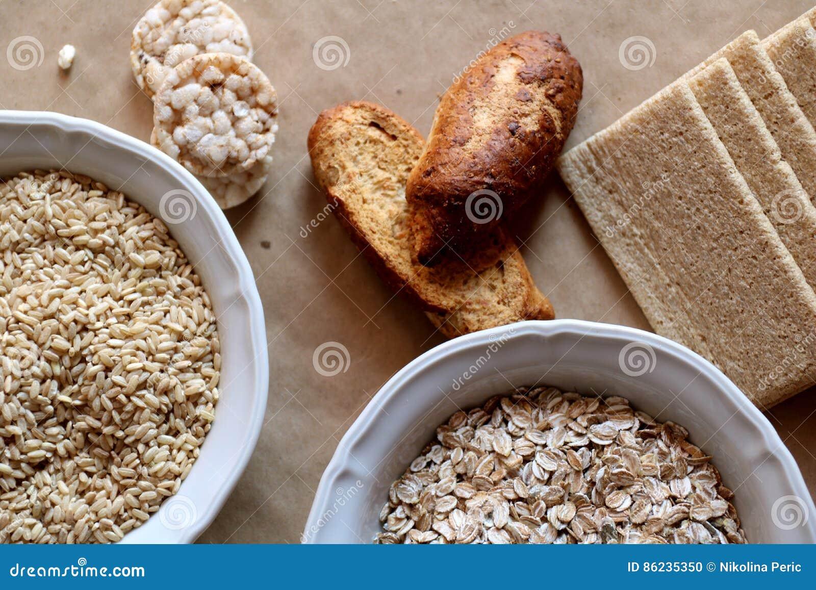 燕麦和米在碗 米糕和面包在背景中 高碳水化合物的食物