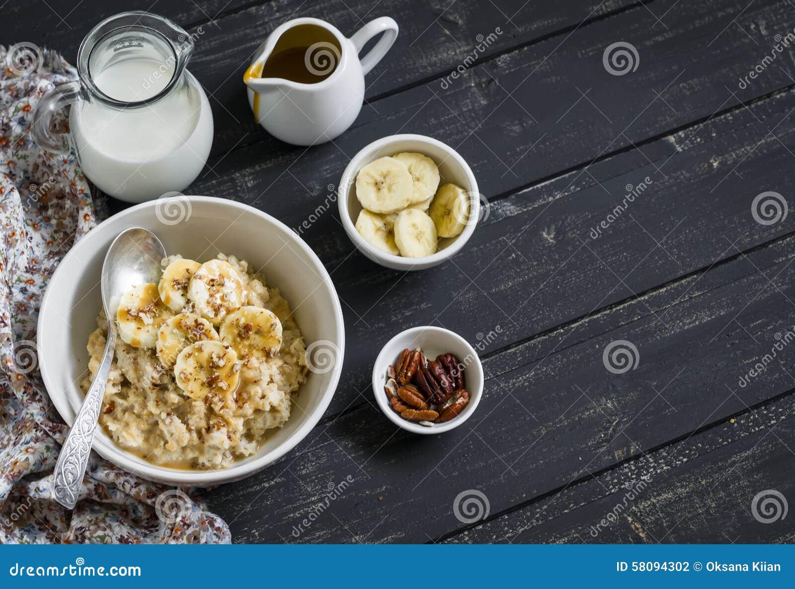 燕麦粥用香蕉、焦糖调味汁和山核桃果在一个白色碗黑暗的木表面上