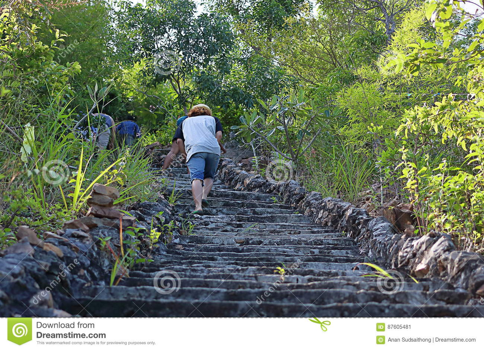 爬上老石楼梯的游人对小山顶