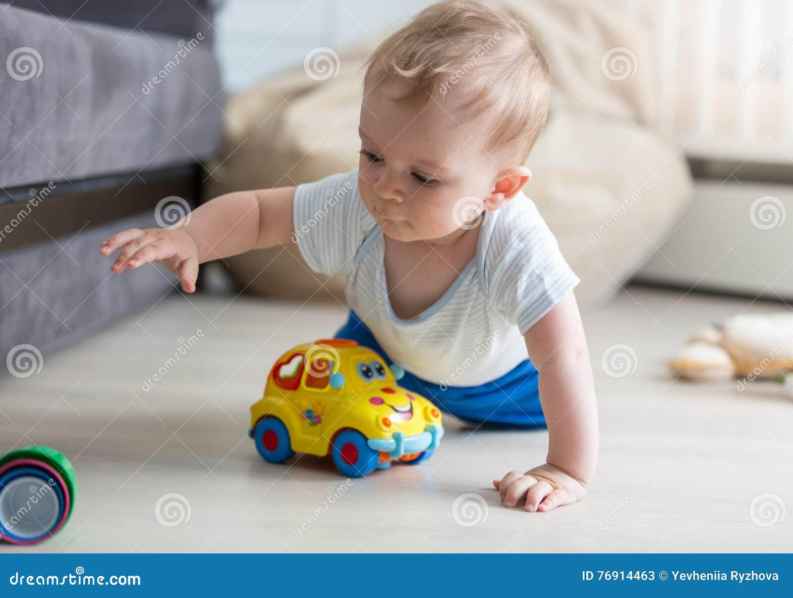 爬行在地板上和使用与玩具的逗人喜爱的男婴画象