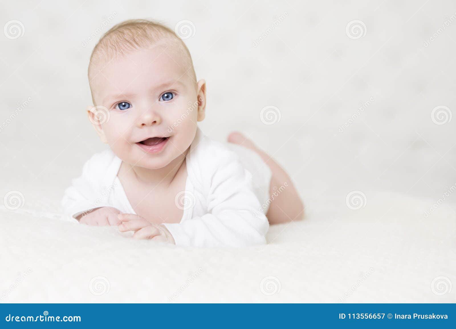 爬行在白色地毯,愉快的小孩男孩画象的婴孩