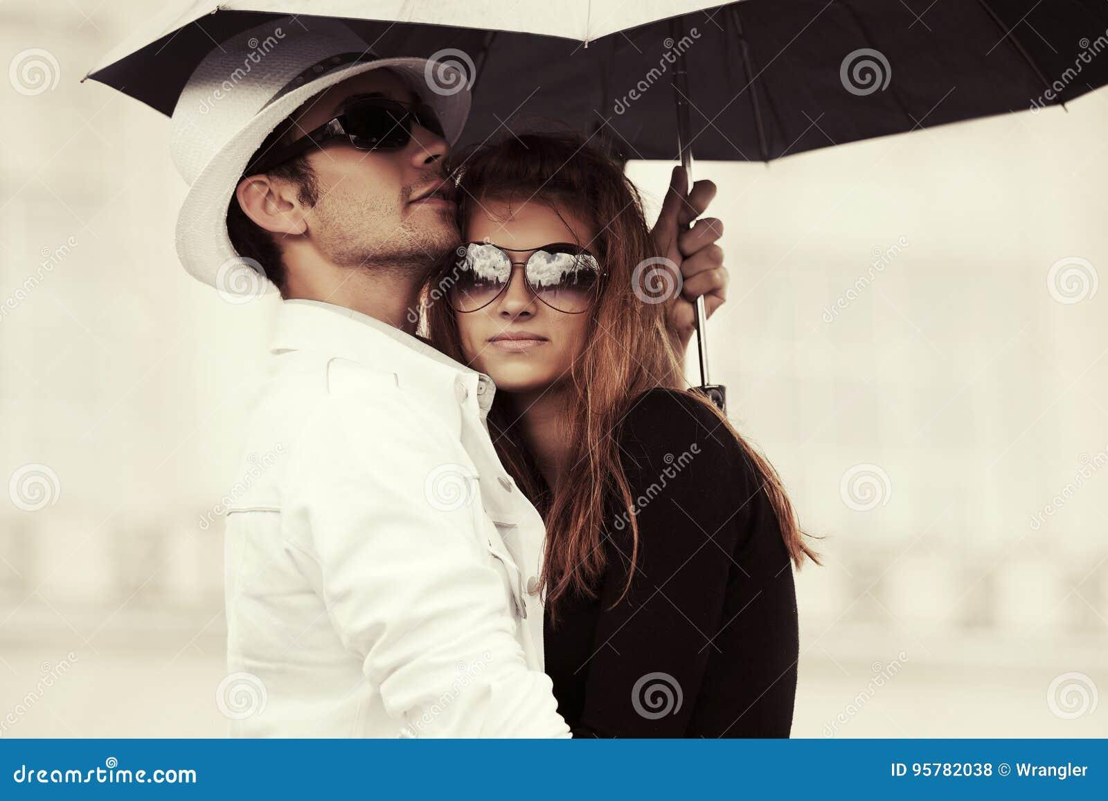 爱上伞的年轻时尚夫妇在城市街道