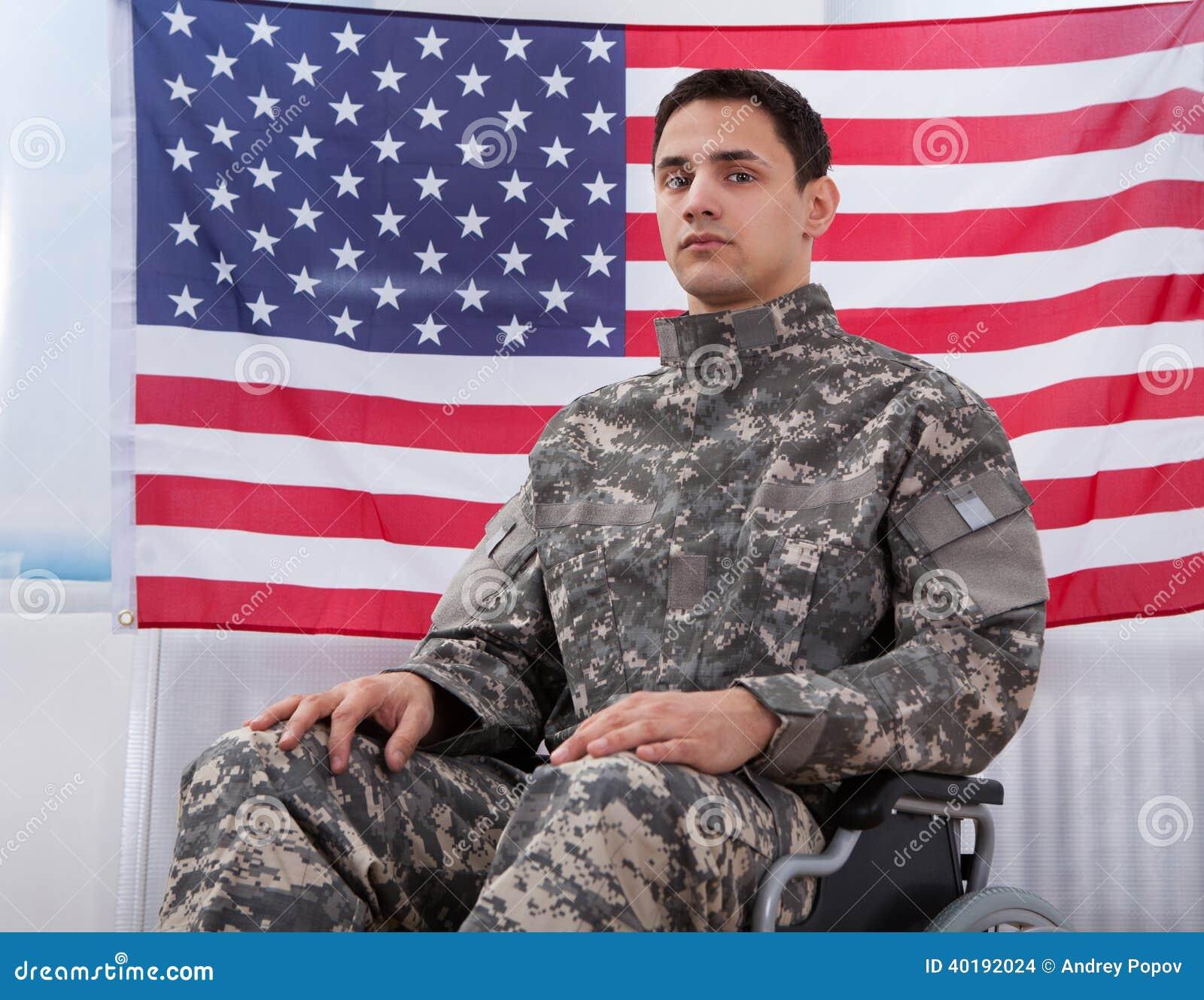 爱国的战士坐轮椅反对美国国旗