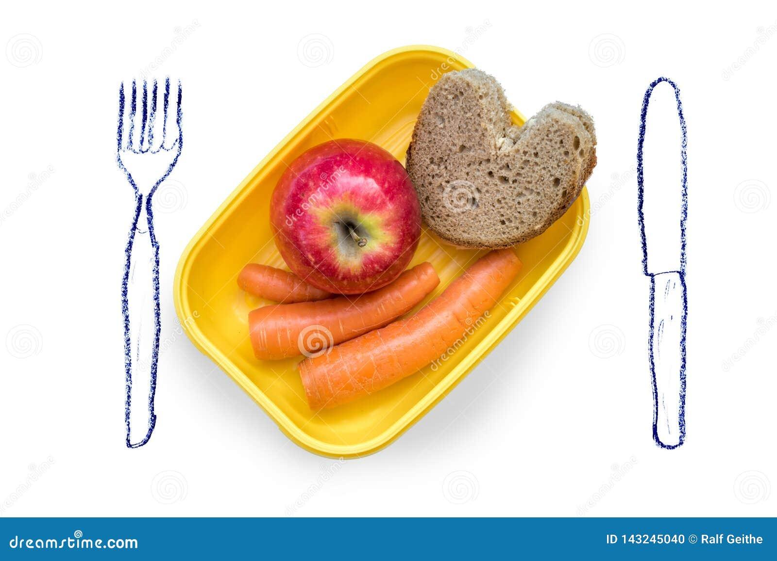 爱恋准备了饭盒用断裂面包、苹果和红萝卜在白色背景与被绘的利器
