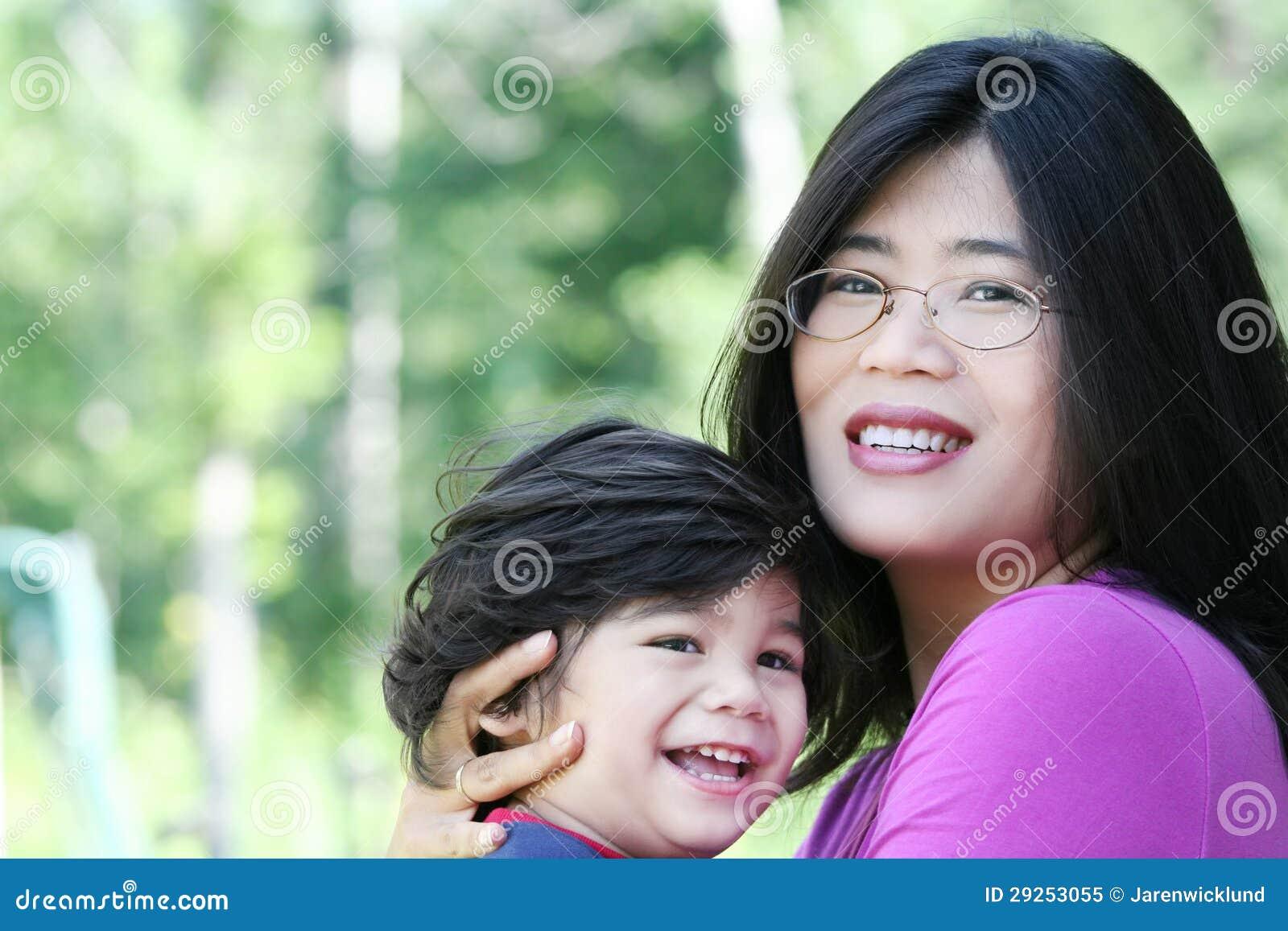 爱恋拿着她的儿子的亚裔母亲
