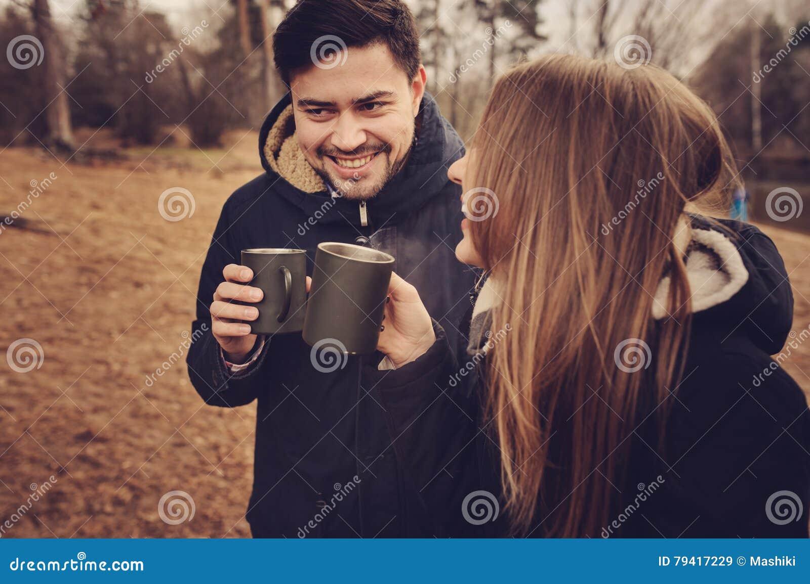 爱恋的年轻夫妇从热水瓶,秋天阵营的愉快的一起室外,饮用的茶