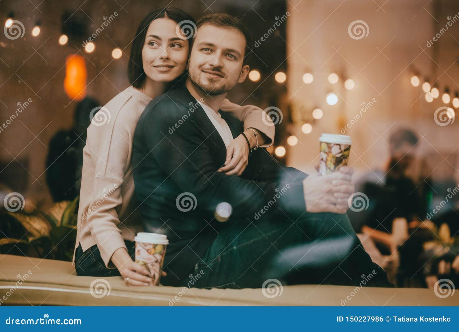 爱的人和女孩拥抱坐在一个浪漫咖啡馆的窗台