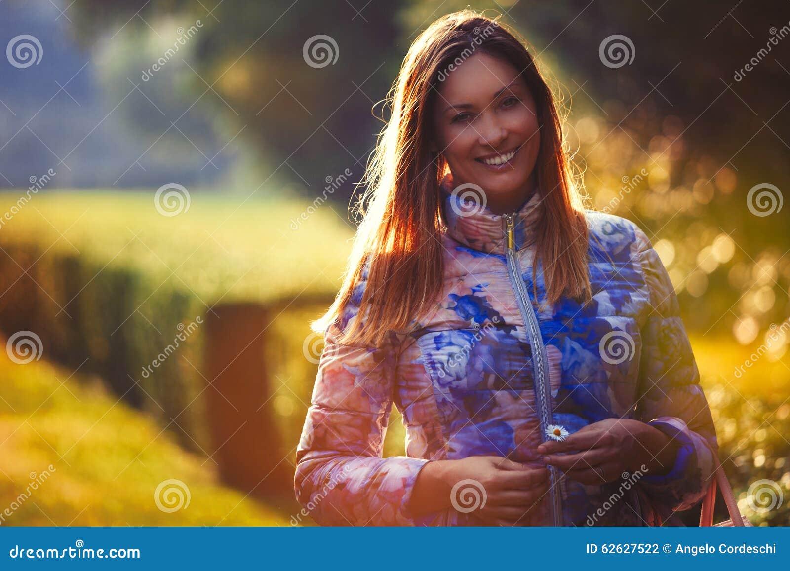 爱的年轻快乐的妇女,室外背后照明 情感和幸福