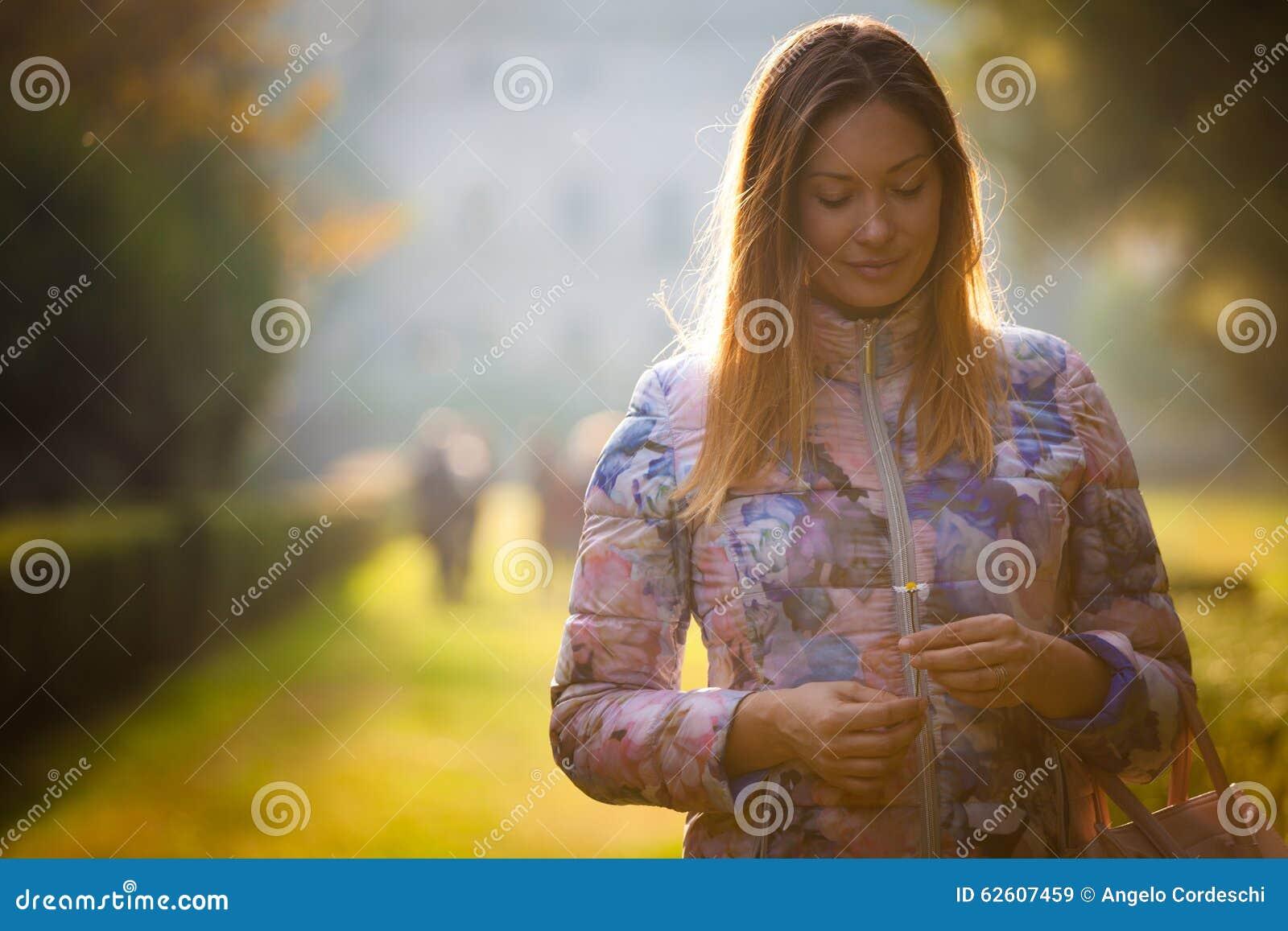 爱的年轻甜妇女,室外背后照明 情感和阴物