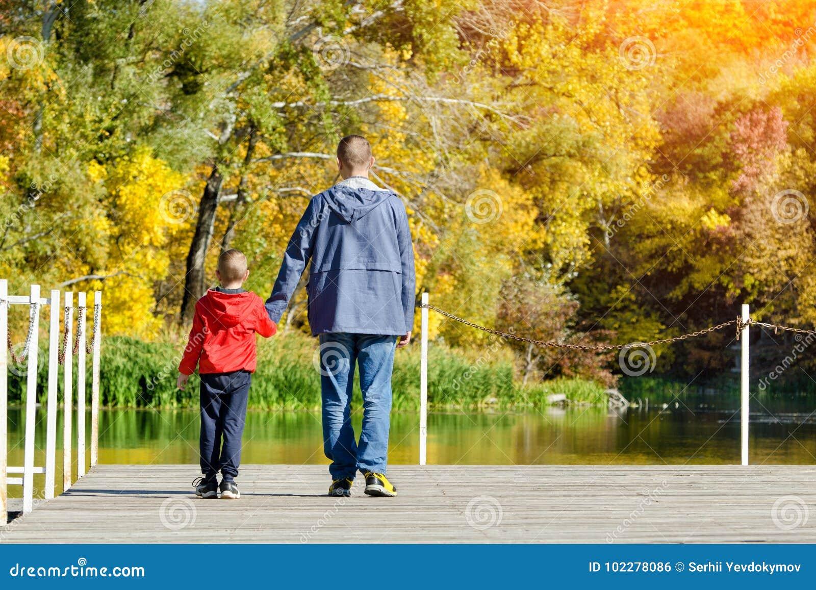 父亲和儿子沿码头走 秋天,晴朗 后面v