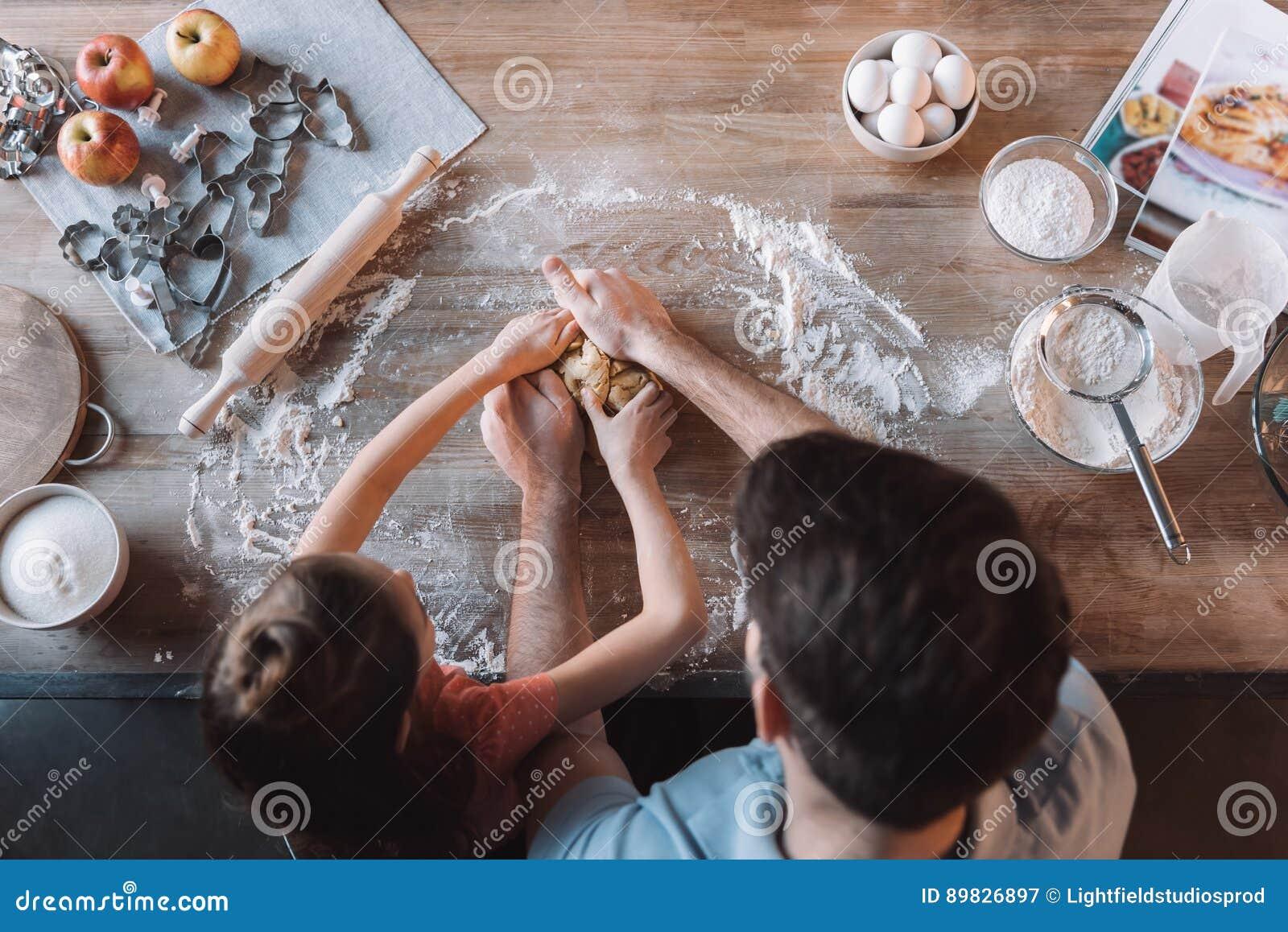 父亲和女儿揉的面团在厨房用桌上