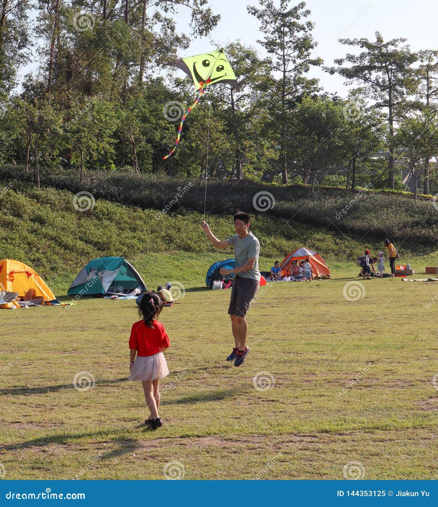父亲和女儿,人们在草在公园,夏天野营在广州,中国
