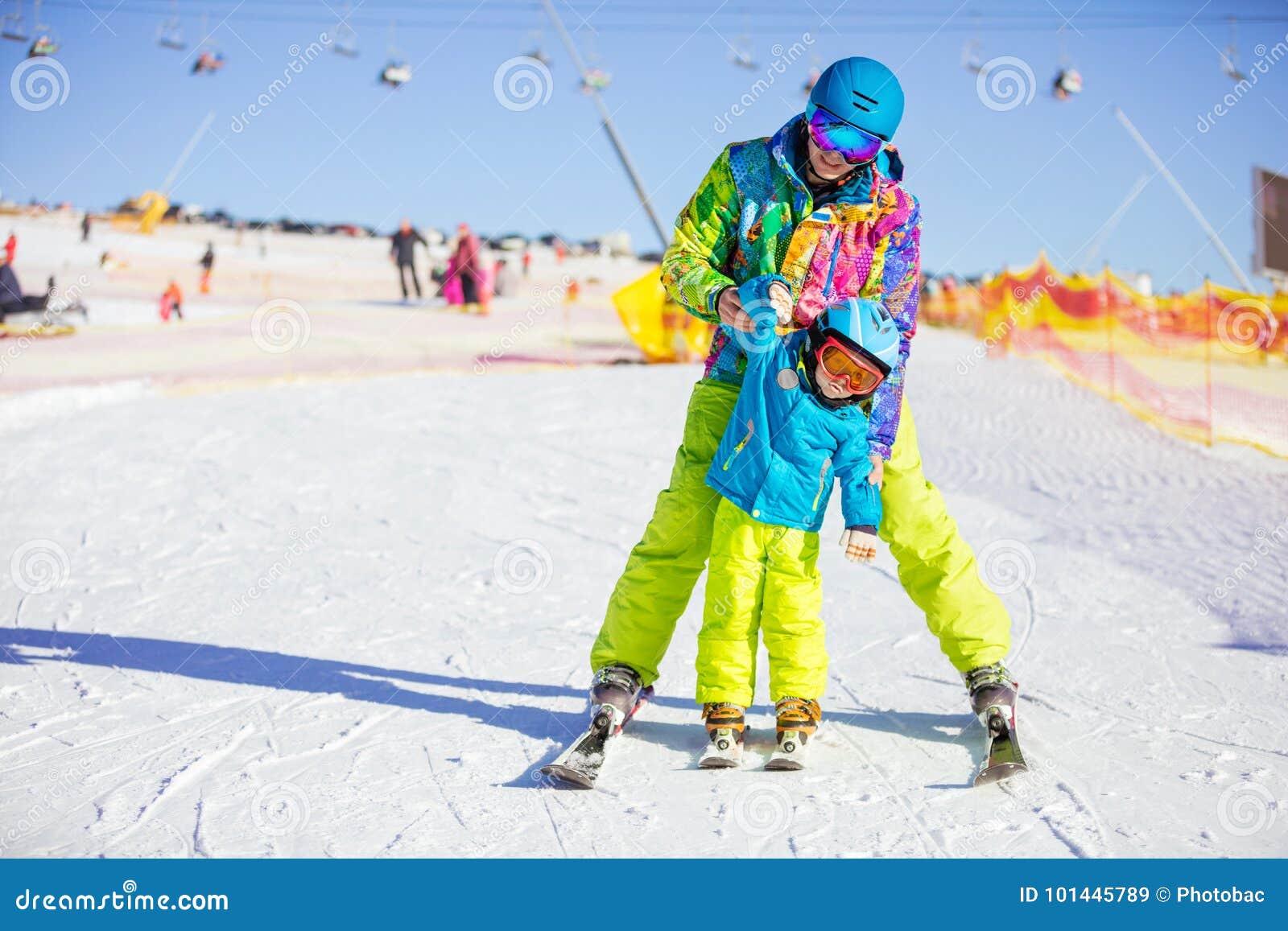 父亲或辅导员教小滑雪者如何做轮