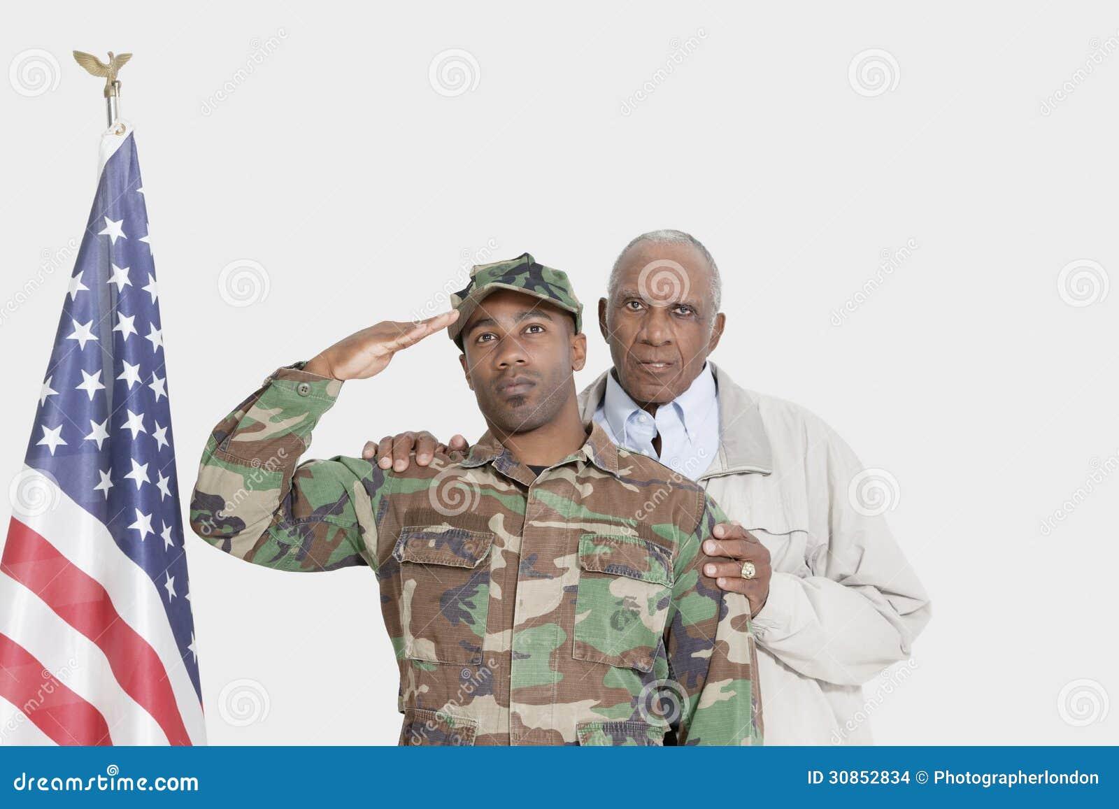 父亲画象有向在灰色背景的美国陆战队战士的美国国旗致敬