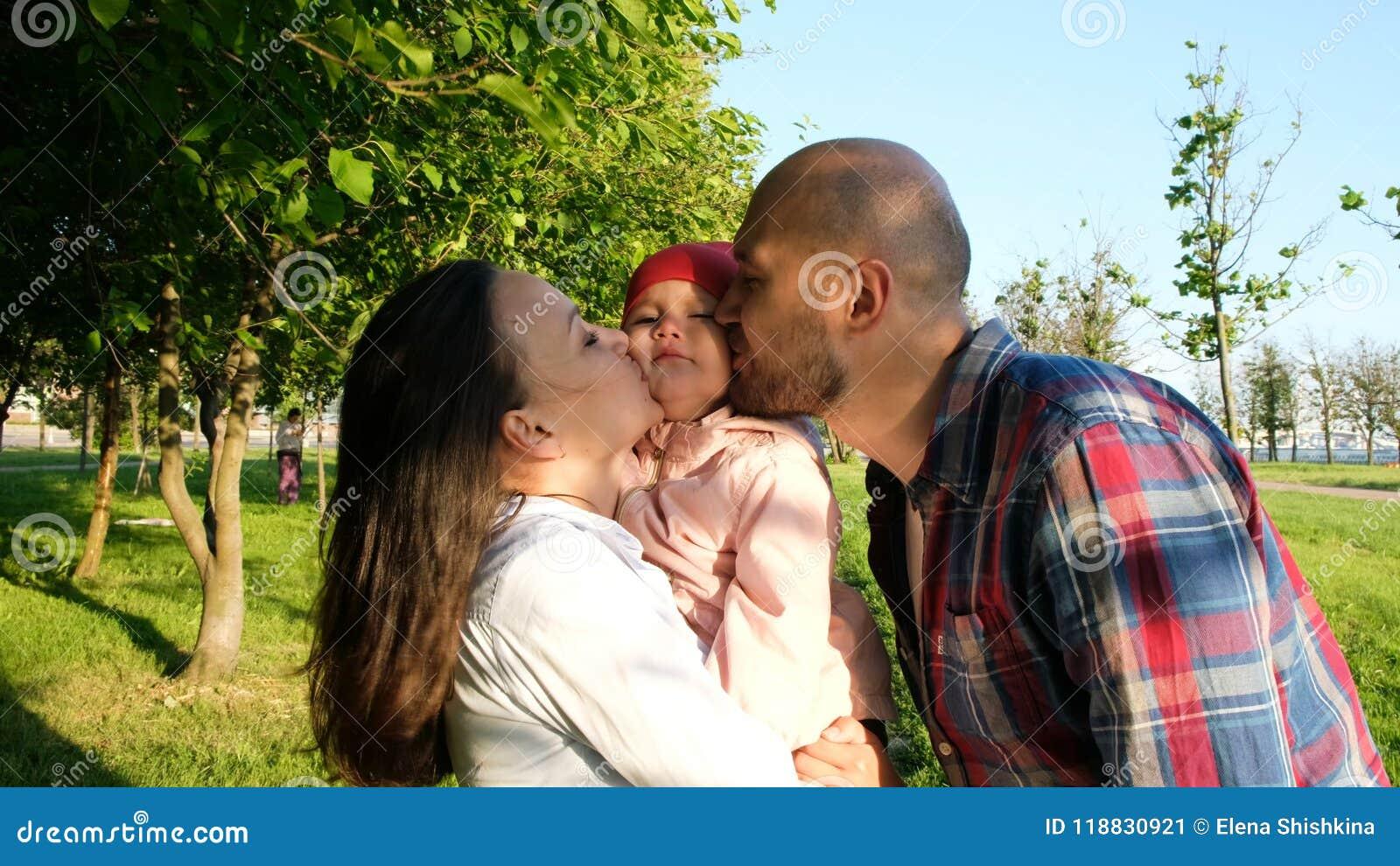 父母亲吻两个面颊的孩子 愉快的年轻家庭有自然的一基于在公园在日落