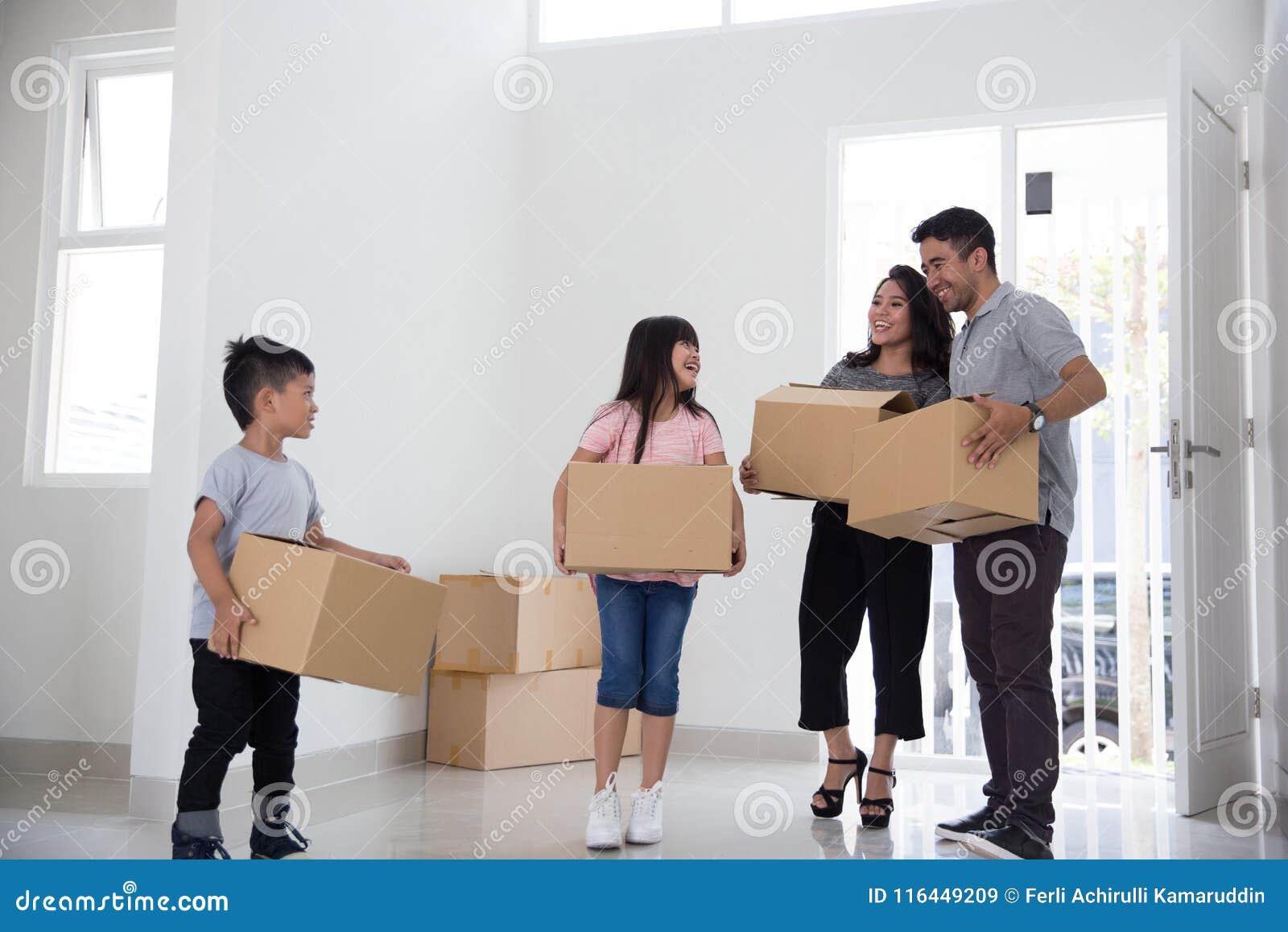 父母和孩子与纸板箱 安置移动新向