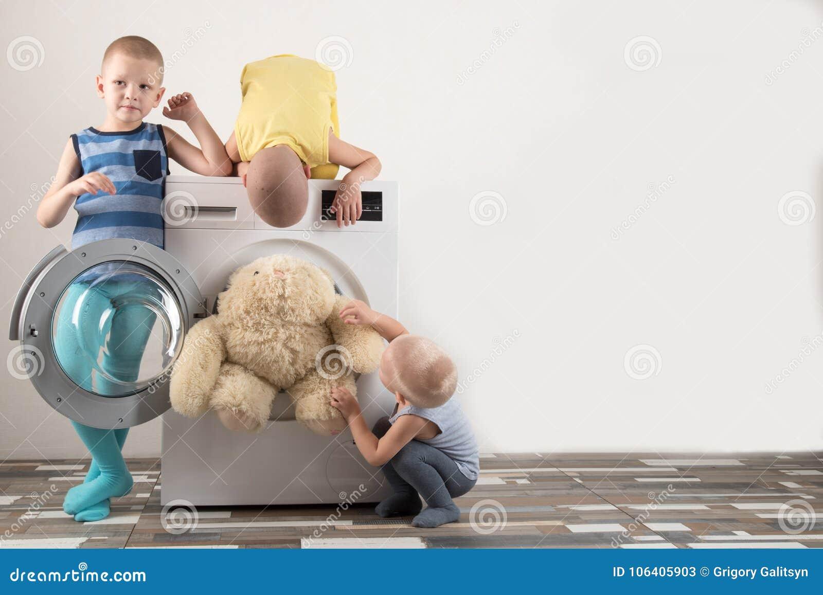 父母被买一台新的洗衣机 孩子设法打开它和洗涤软的玩具 愉快的男孩在家使用