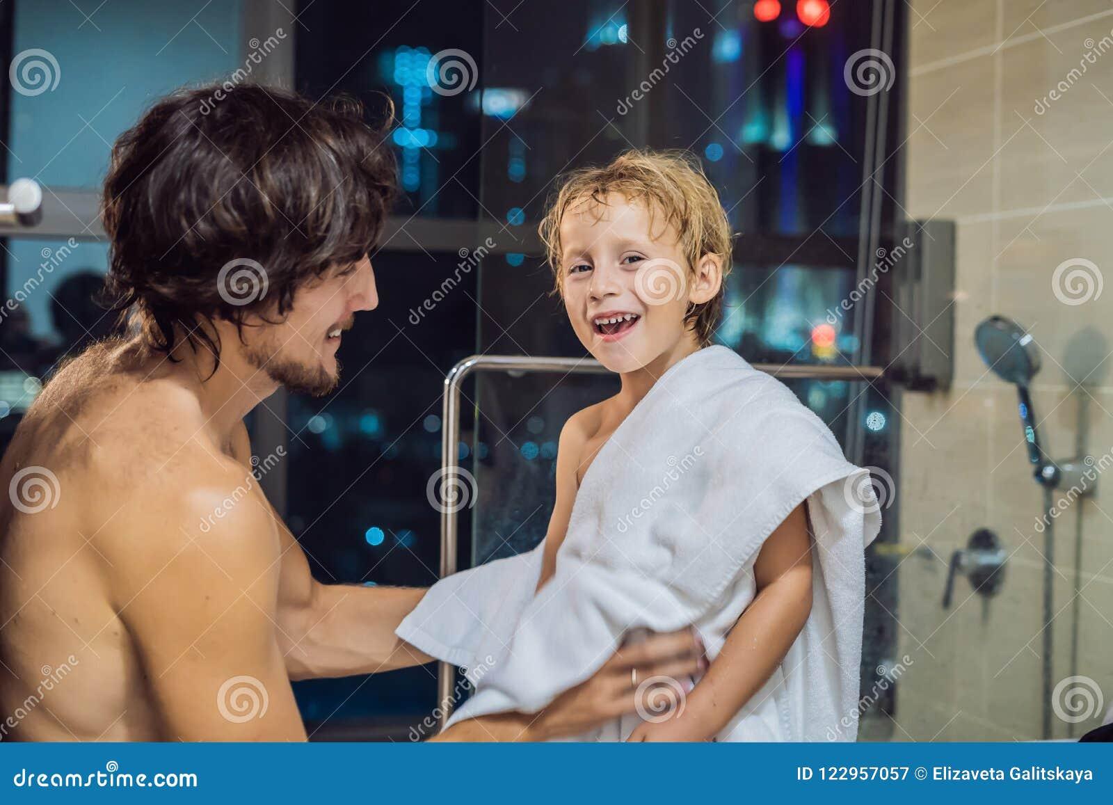 爸爸在一个窗口的背景抹他的儿子与毛巾在一场阵雨以后在晚上在去前睡与全景的