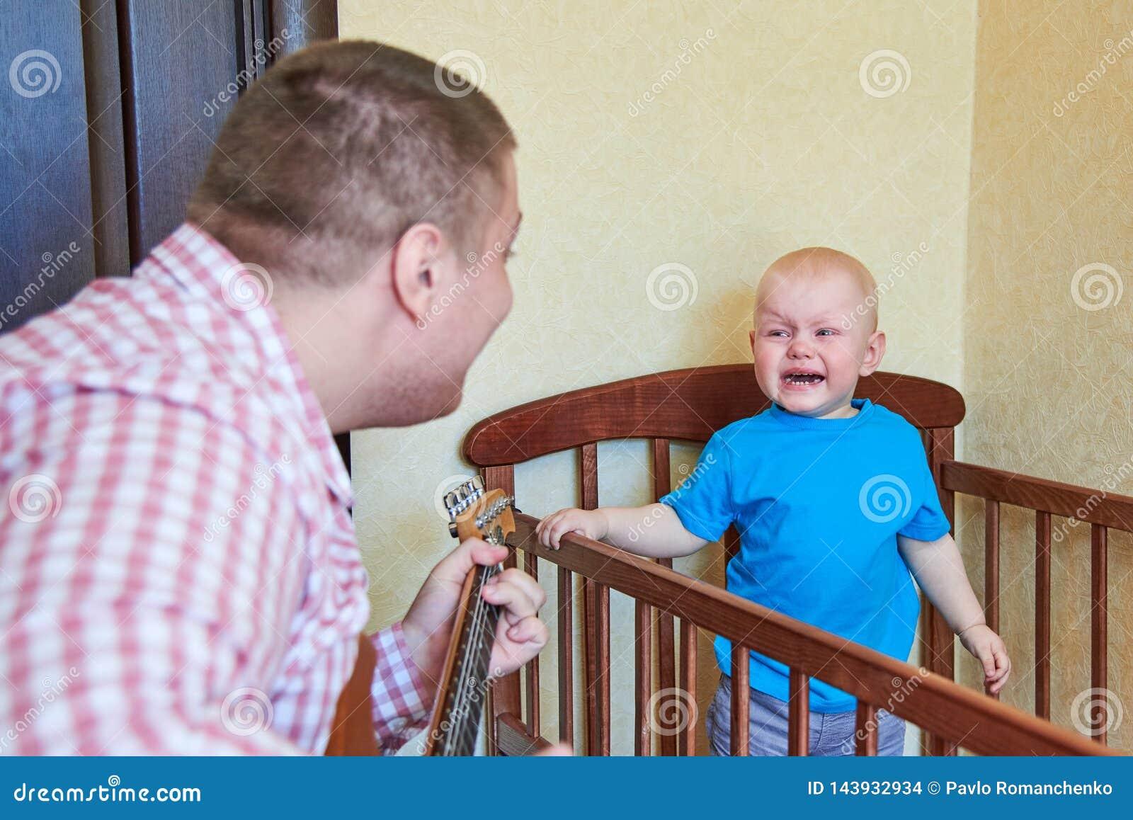 爸爸弹吉他慰问他哭泣的儿子