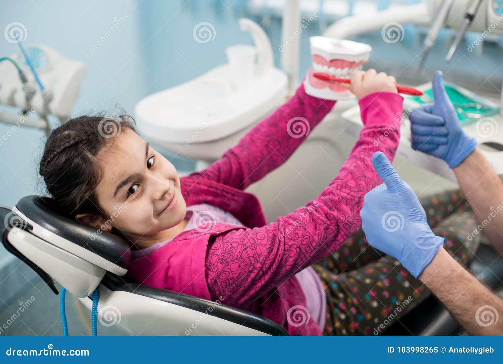 牙医椅子的愉快的女孩教育关于适当牙掠过的在牙齿诊所 牙科,口腔卫生概念