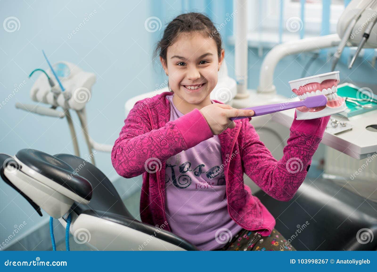 牙医的微笑的女孩主持显示适当牙掠过使用牙齿下颌模型和大牙刷在牙齿诊所