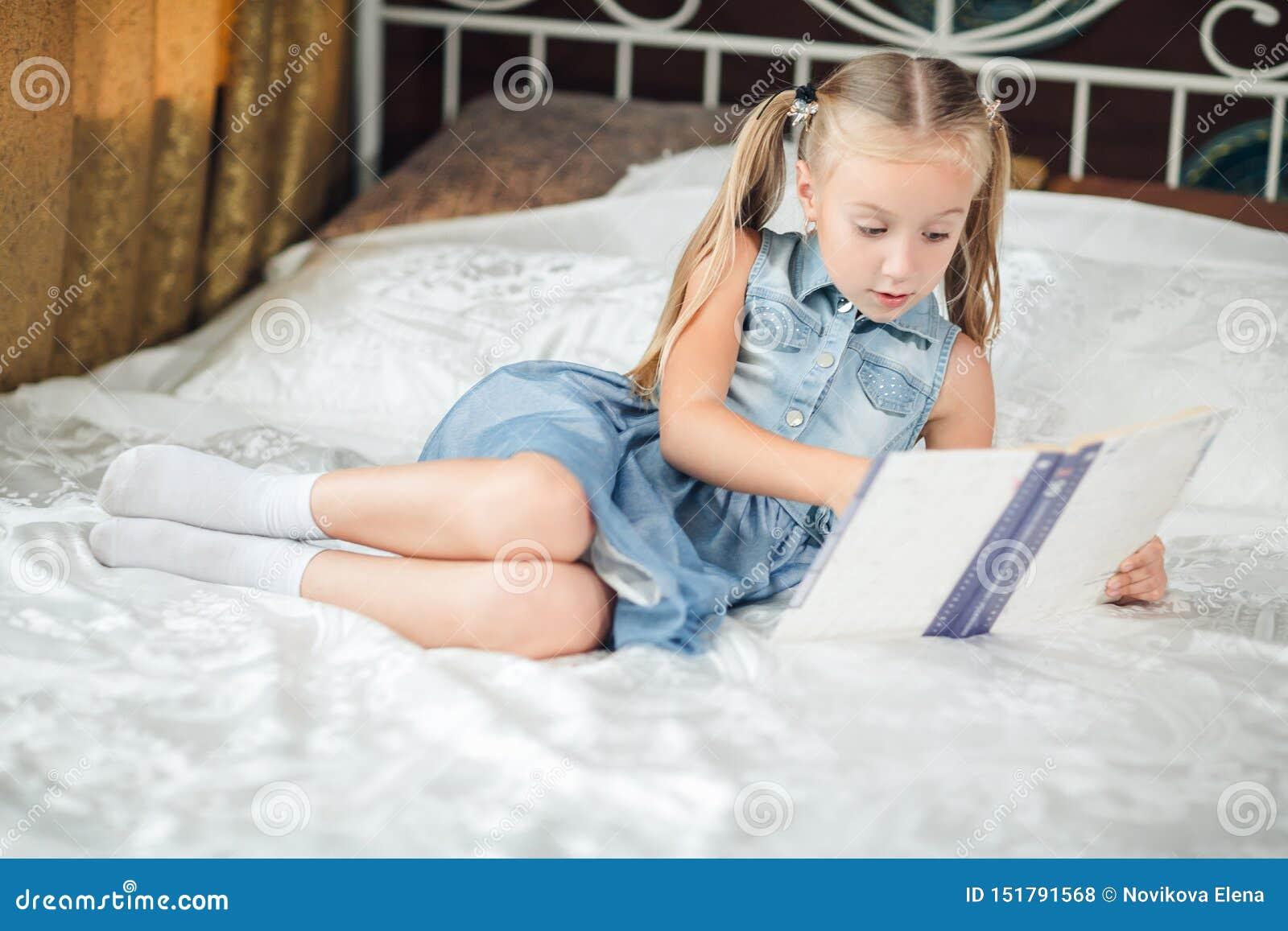 牛仔布sundress看书的逗人喜爱的女孩在床上在家