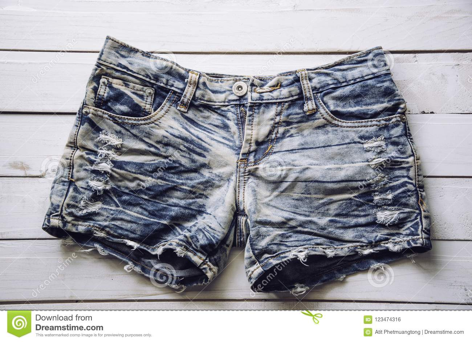 牛仔裤短裤在白色木地板被安置
