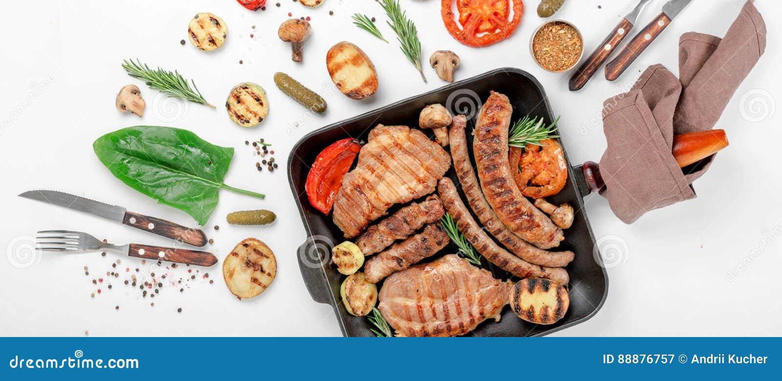 牛排和香肠在与烤菜的格栅烹调了