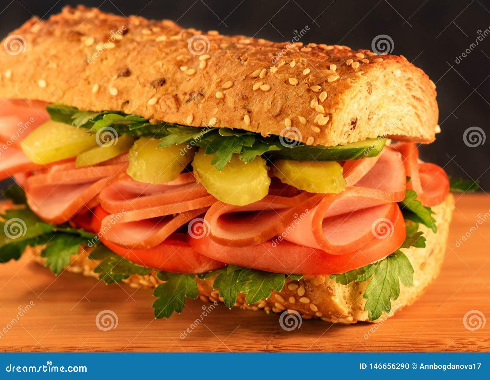 特写镜头三明治用火腿、酱瓜、蕃茄和绿色 芝麻小圆面包