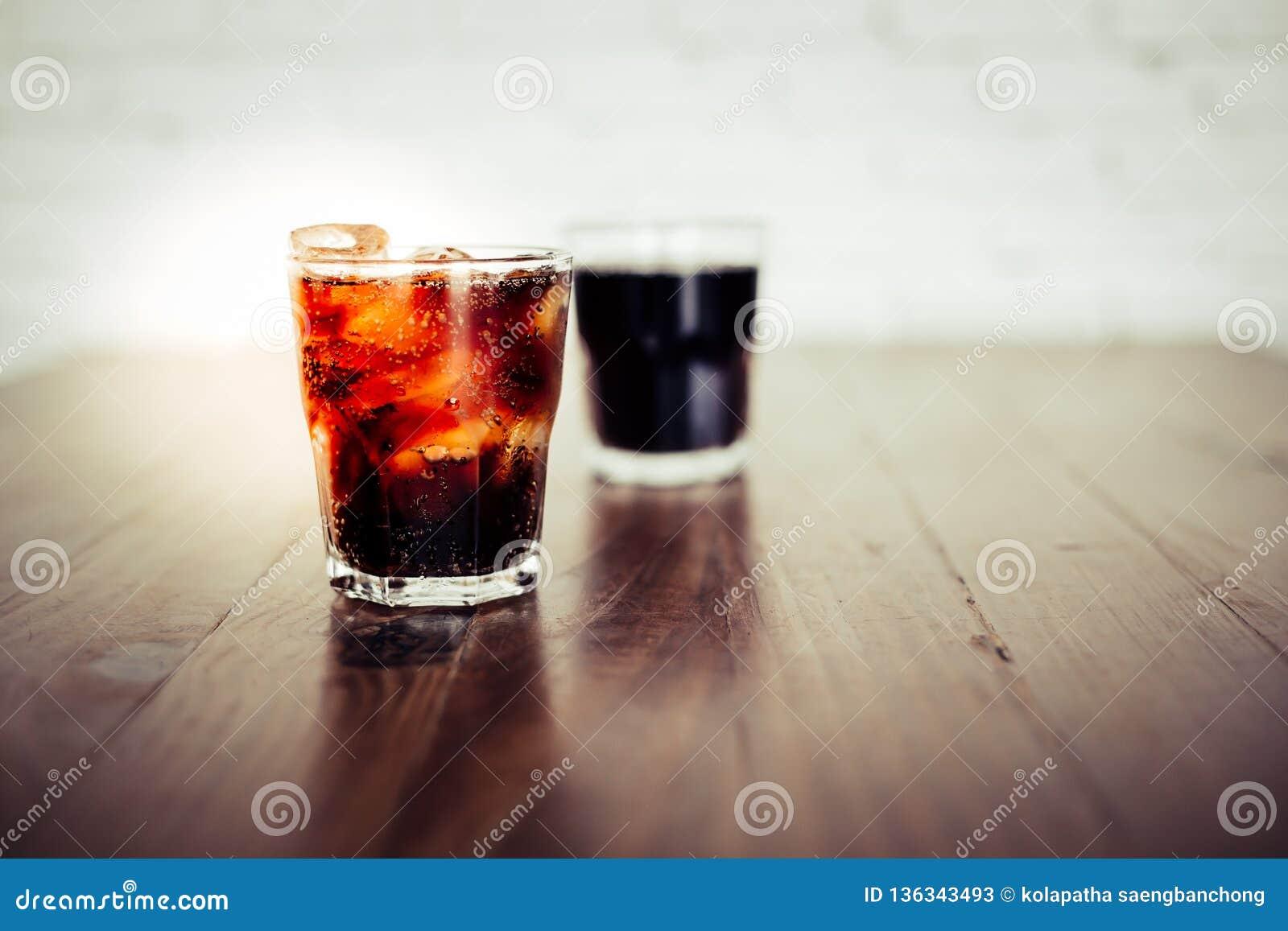 特写镜头可乐或汽水 在一块玻璃的冷的可乐与在木桌上的冰块 可乐口味是很可口的,当您
